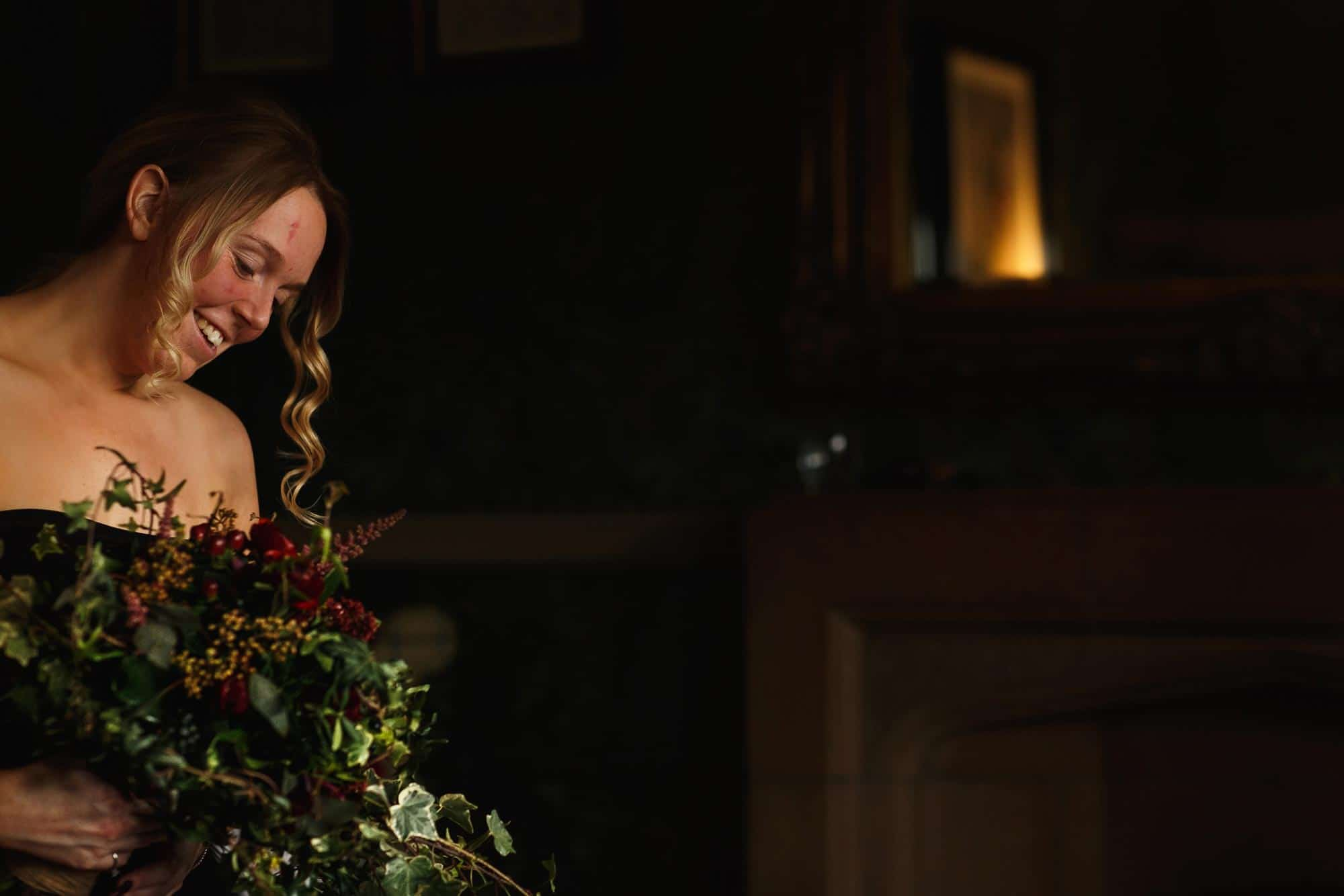 Bride admiring her wedding flowers at Mitton Hall