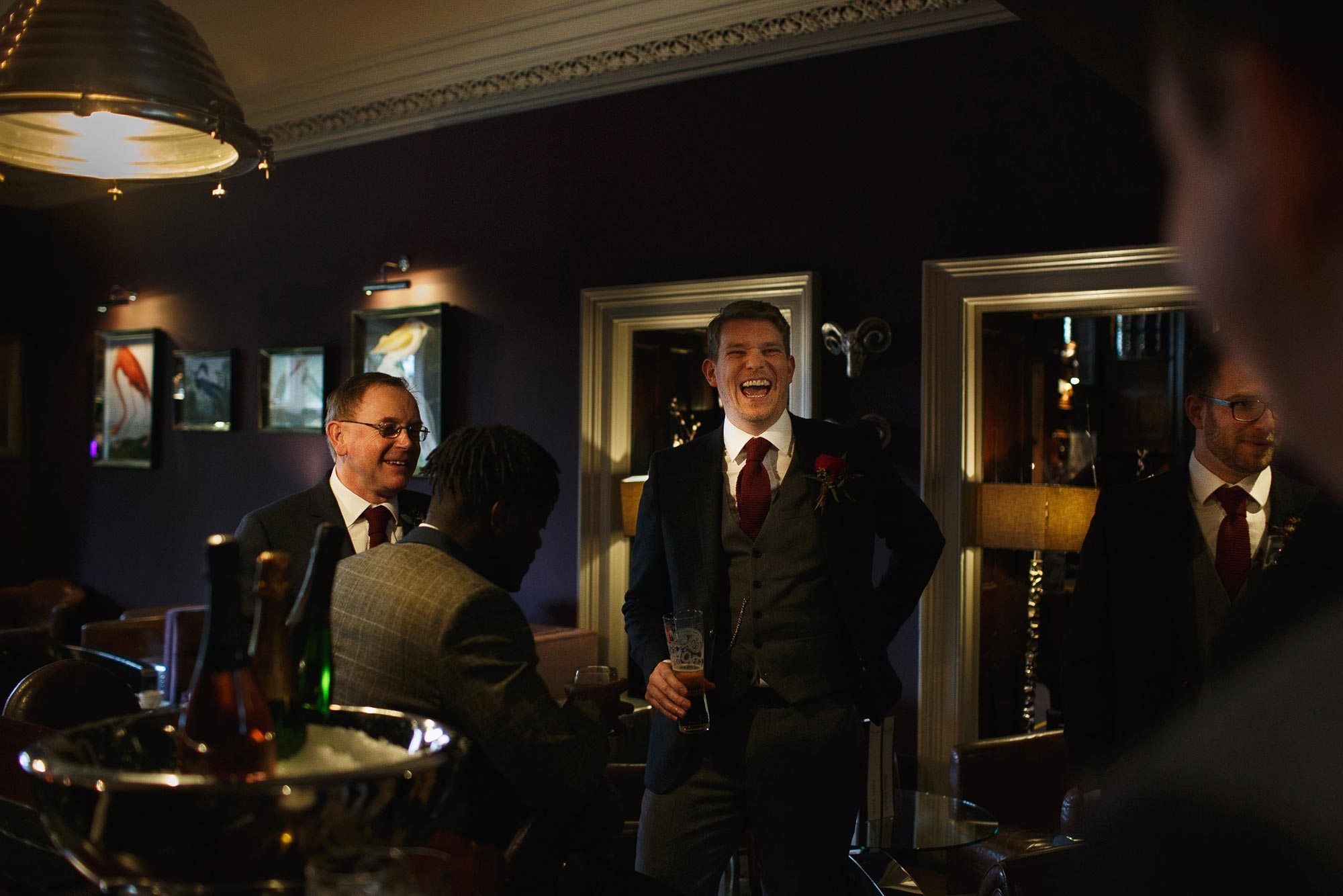 Groom drinking whiskey at the bar with his friends at Mitton Hall