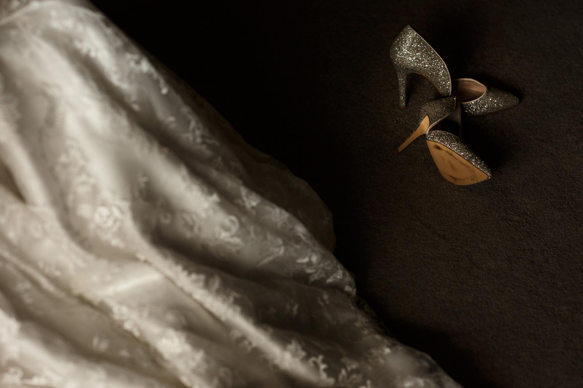 Brides wedding shoes on the floor next to her dress at Mitton Hall