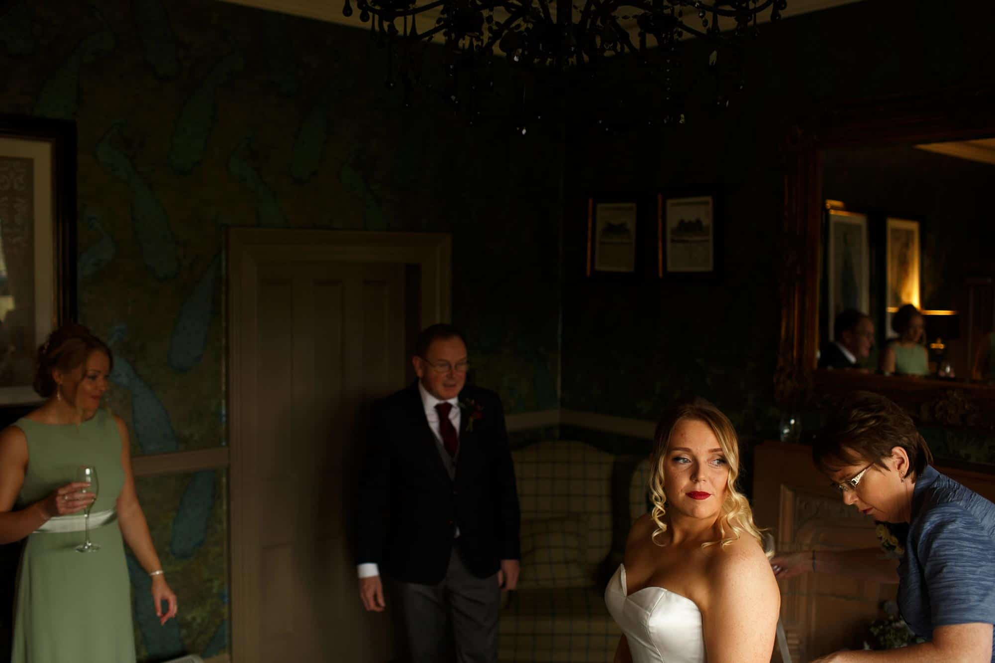 Bride getting into her dress in the bridal suite at Mitton Hall whilst her family watch