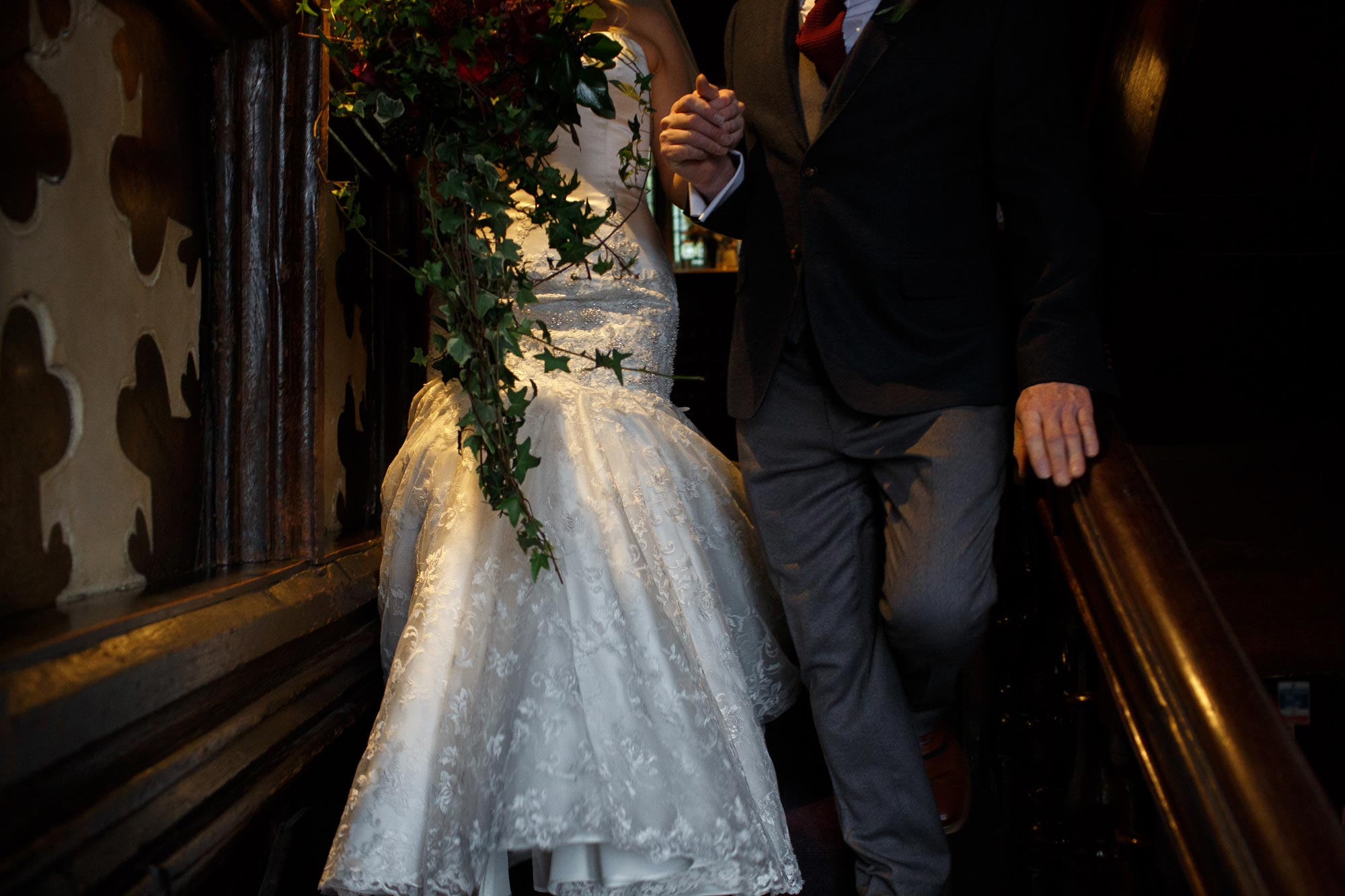 Bride walking down the stairs inside Mitton Hall hand in hand with her Dad
