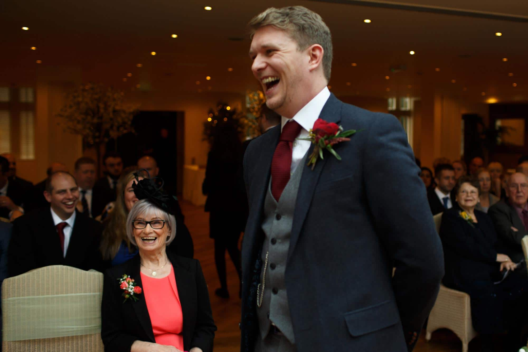Groom laughing whilst he waits or his bride at Mitton Hall
