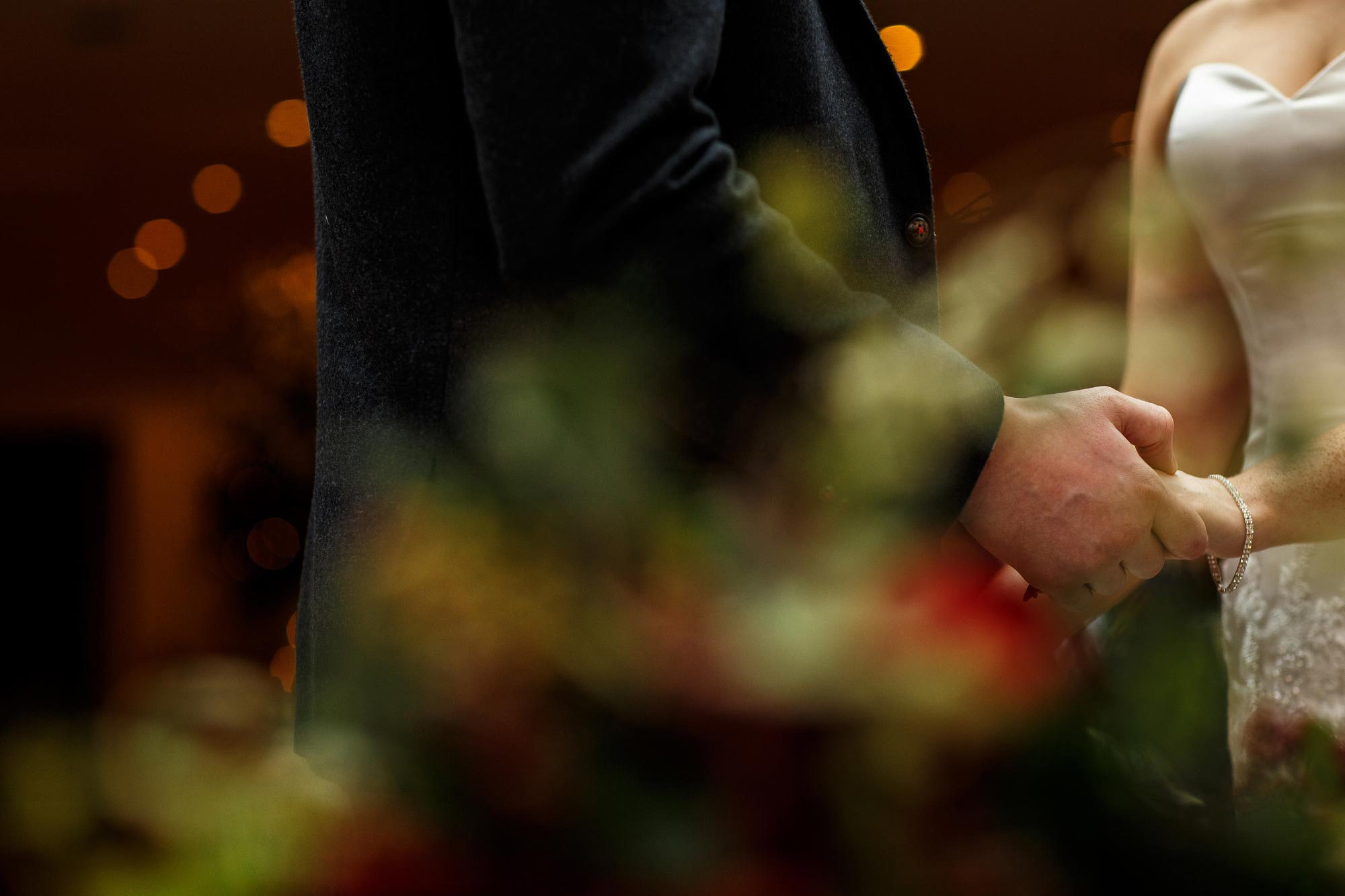 Close up of the bride and grooms hands as they exchange rings at Close up of the Bride and Groom saying their vows inside the conservatory at Mitton Hall wedding ceremony