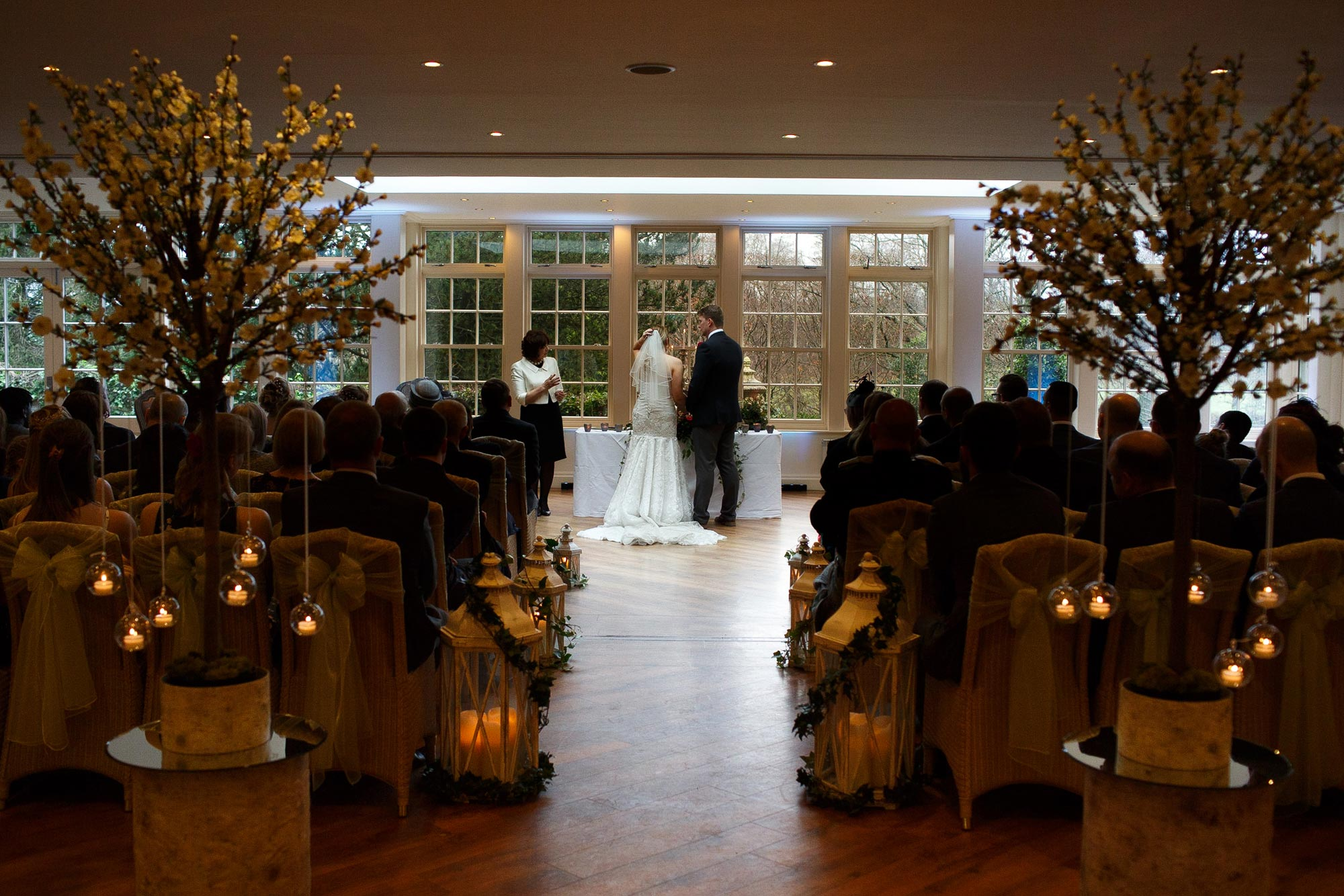 Photograph of the ceremony room at Close up of the Bride and Groom saying their vows inside the conservatory at Mitton Hall with the bride and groom at the top of the aisle