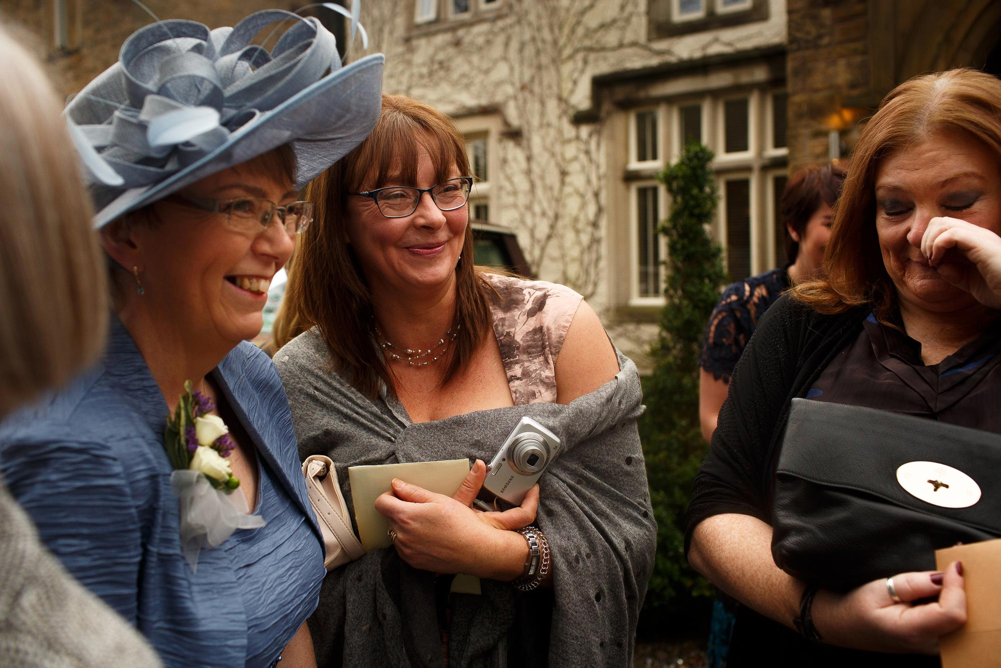 Wedding guest laughing outside Mitton Hall wedding