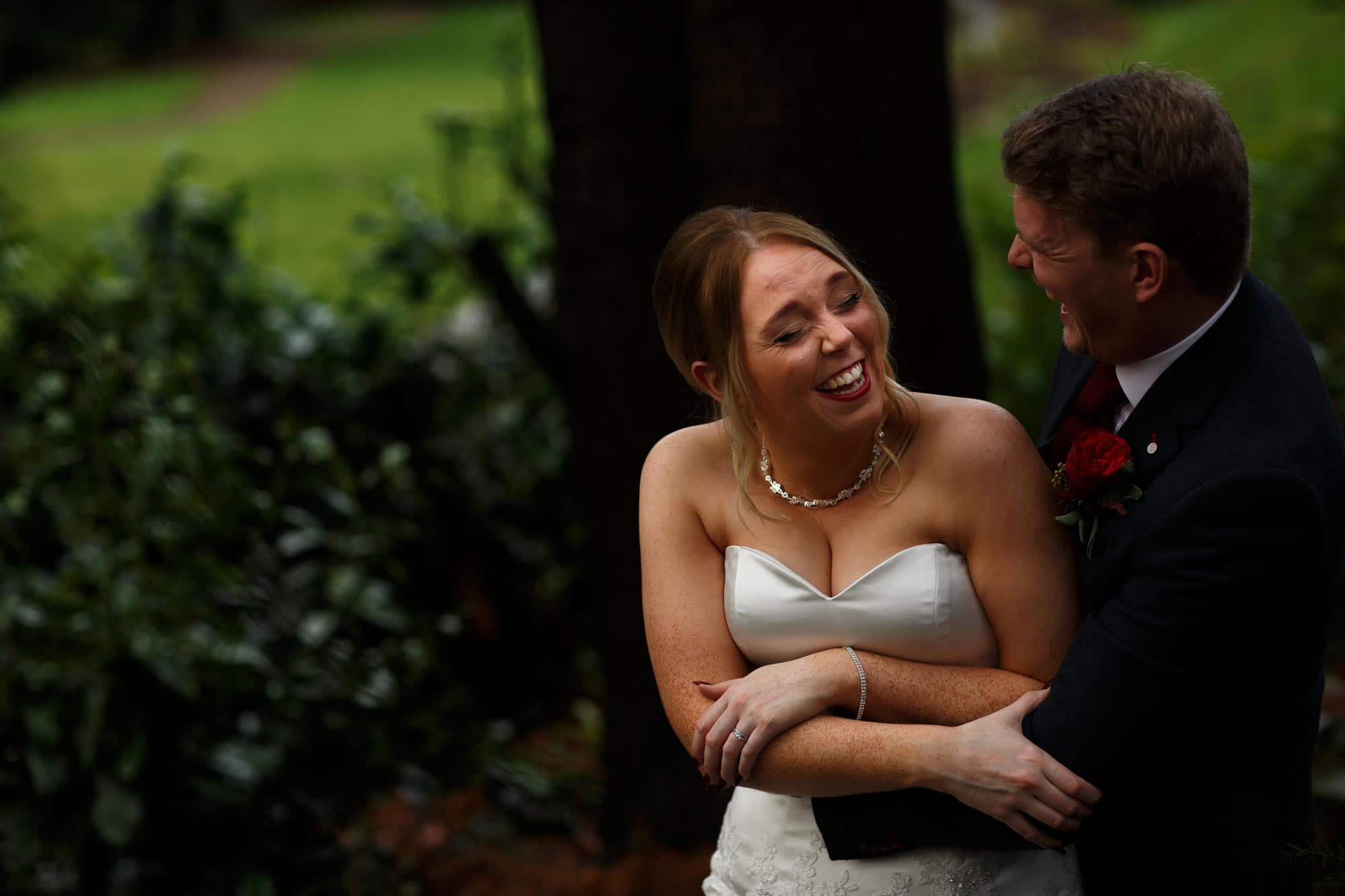 Bride and groom laughing outside in the gardens of Mitton Hall