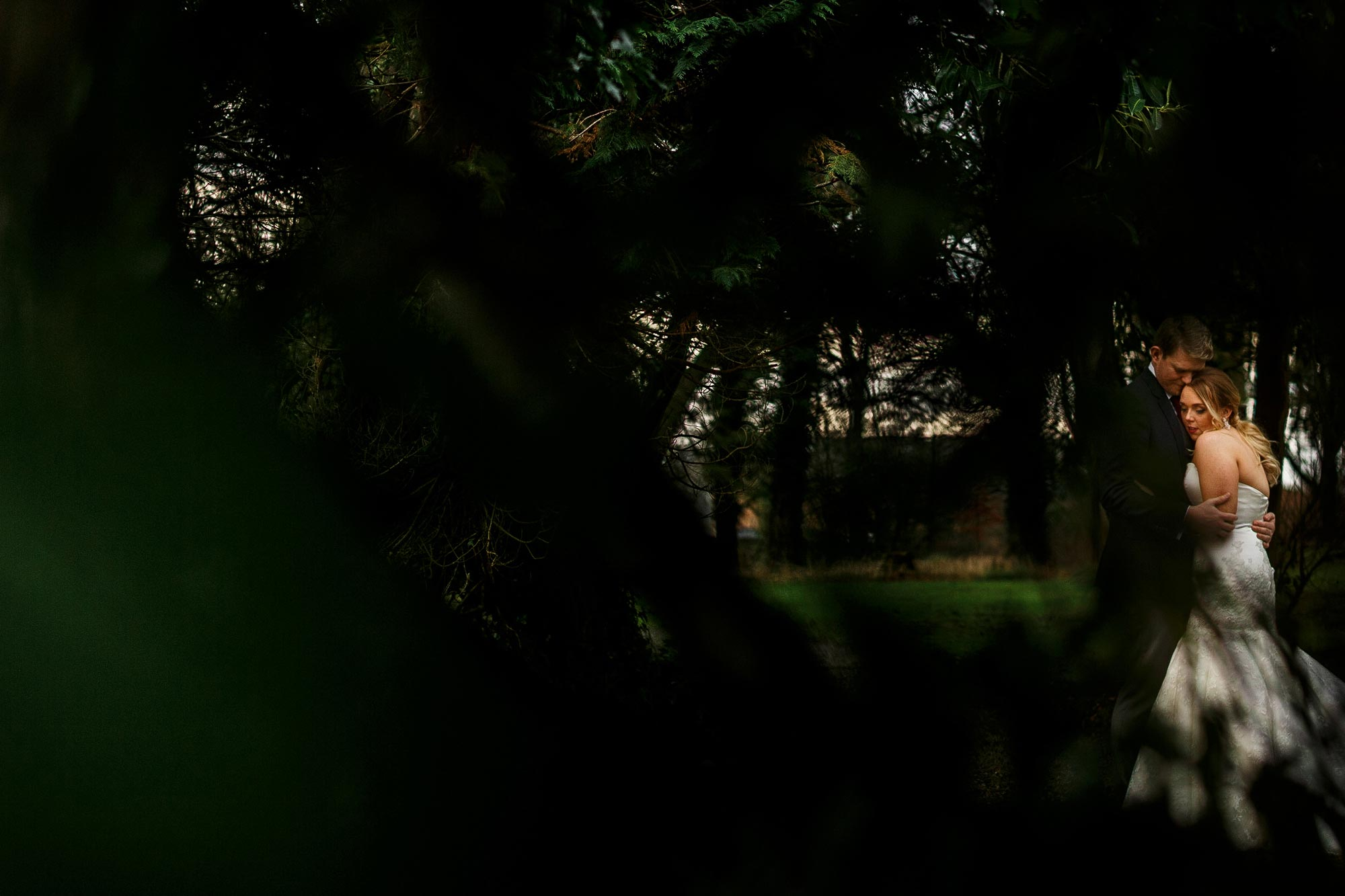 Wedding photograph of bride and groom through the trees in the gardens at Mitton Hall