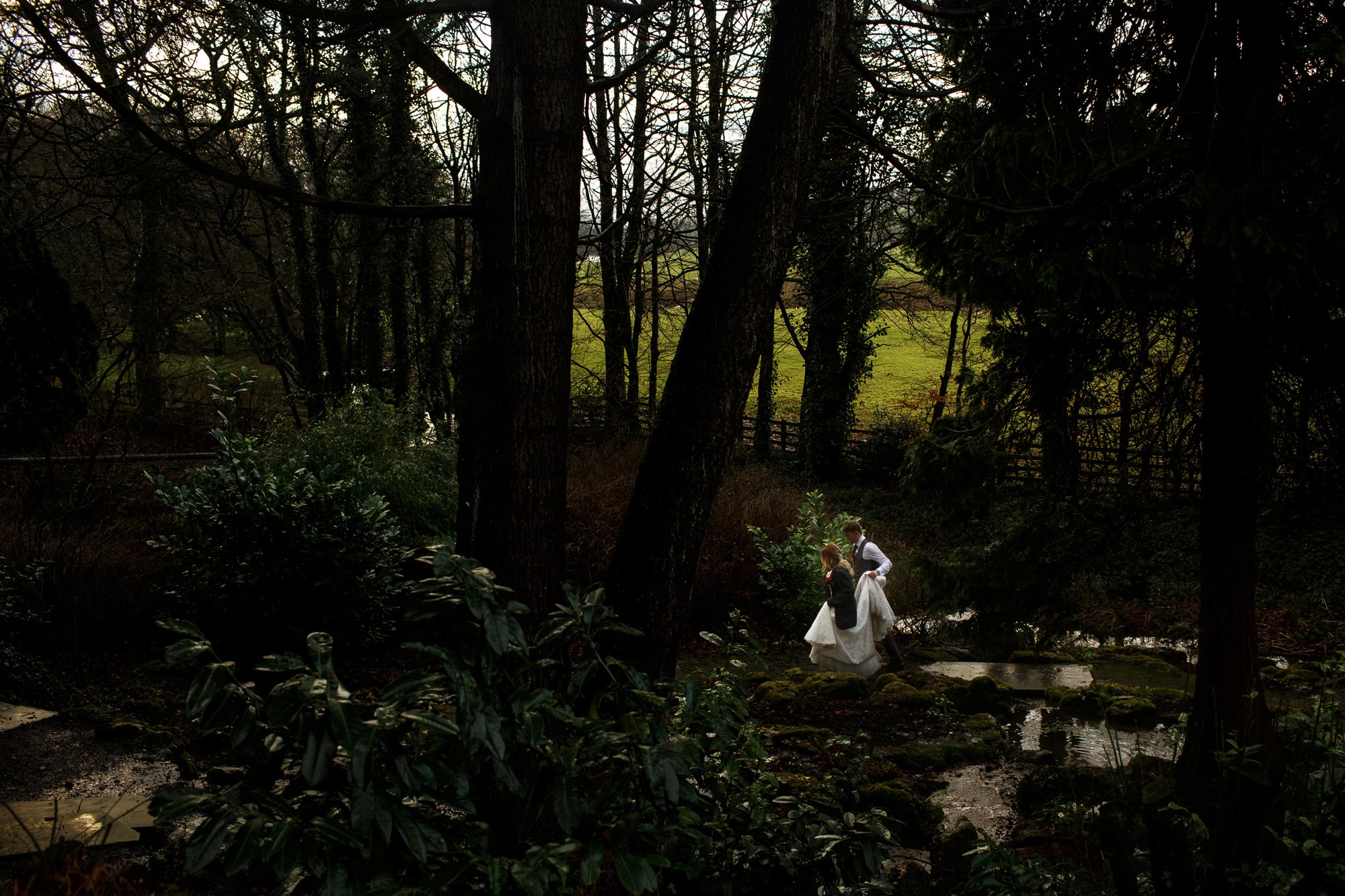 Bride and groom walking through the gardens of Mitton Hall on their wedding day