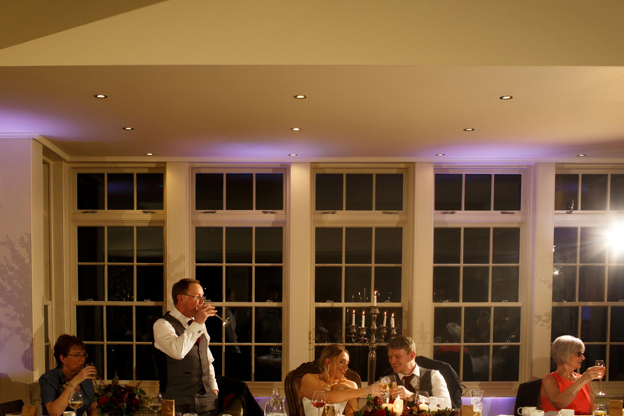 Bride and groom clinking glasses during the wedding speeches at Mitton Hall