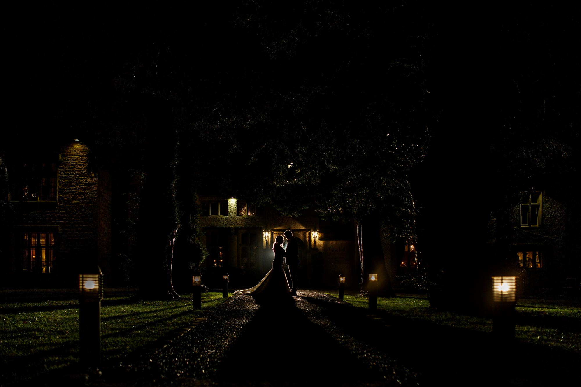 Wedding photograph of a bride and groom outside Mitton Hall at night