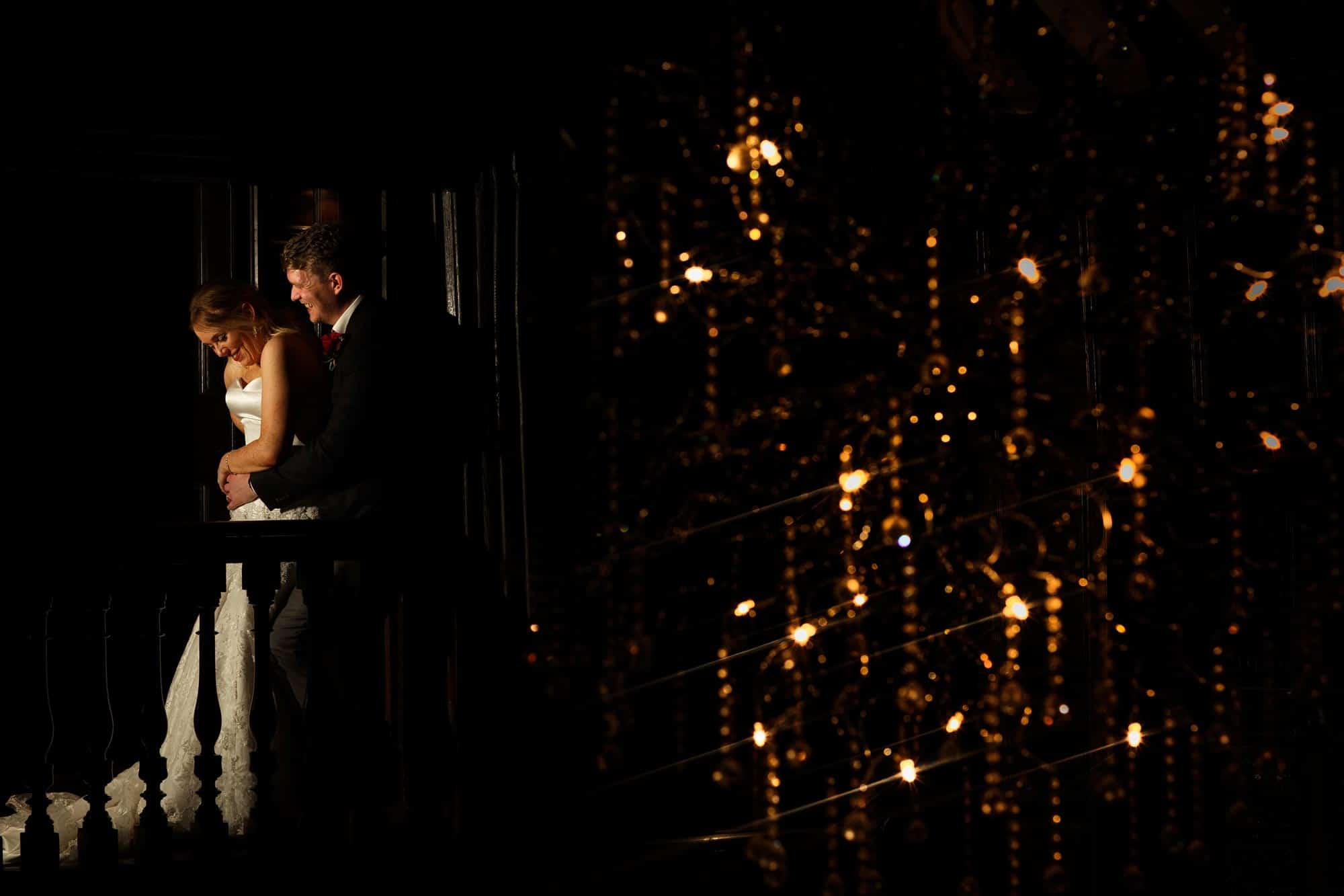 Wedding photograph of the Bride and Groom in front of the Chandelier at Mitton Hall