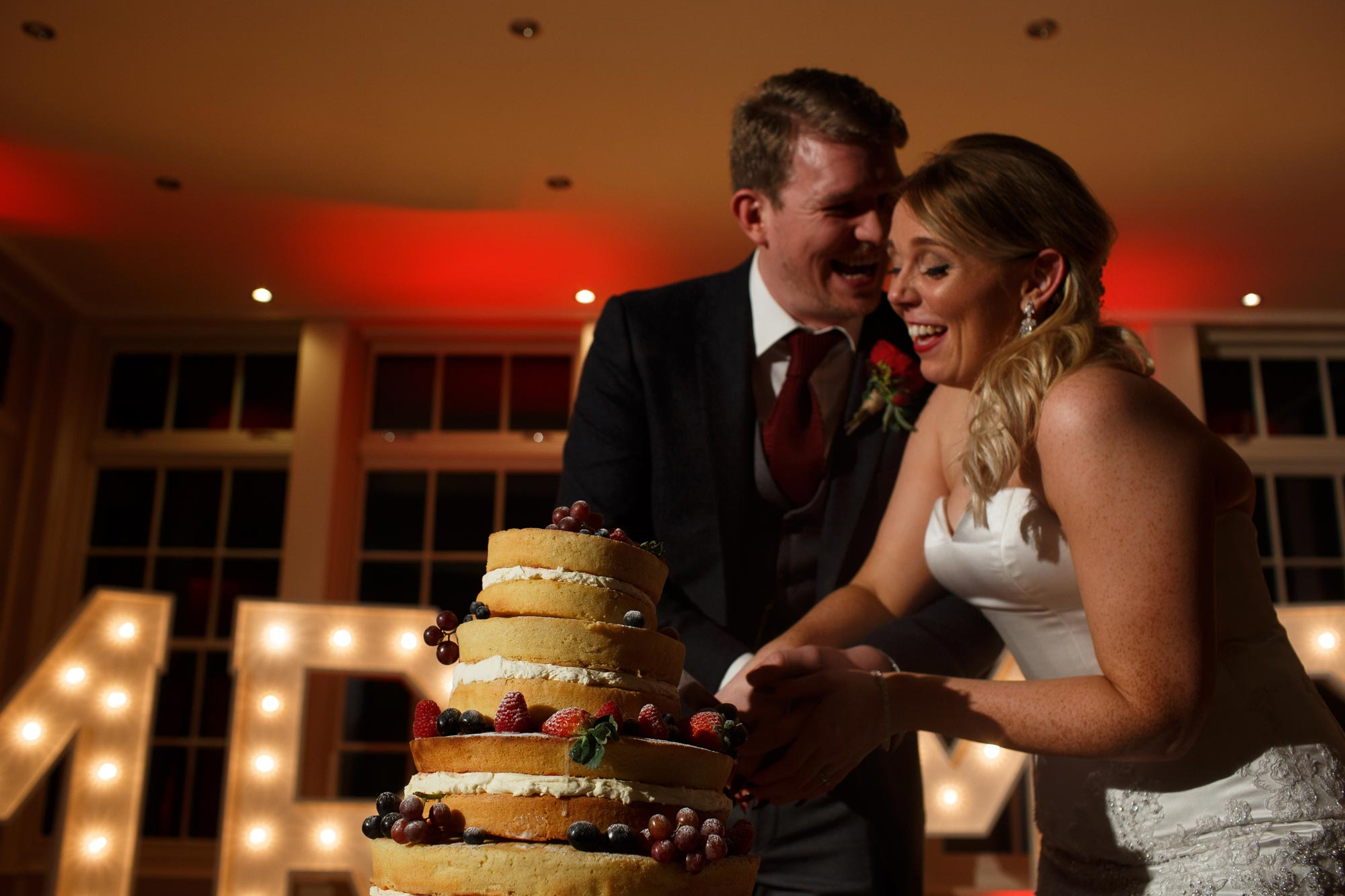 Bride and groom laughing as they cut the cake at their Mitton Hall wedding