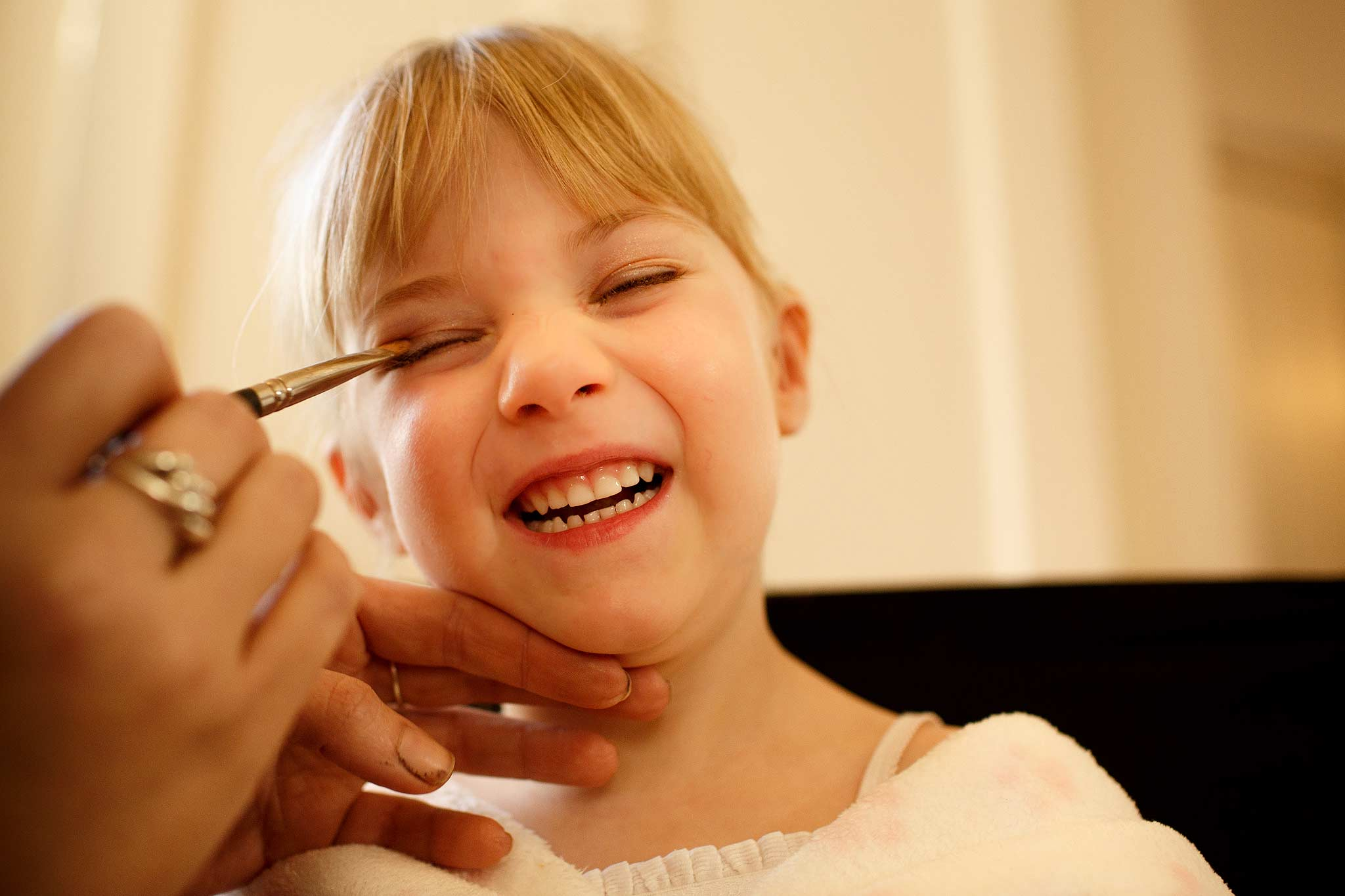Flower girl laughing as the make up brush tickles her at Samlesbury Hall