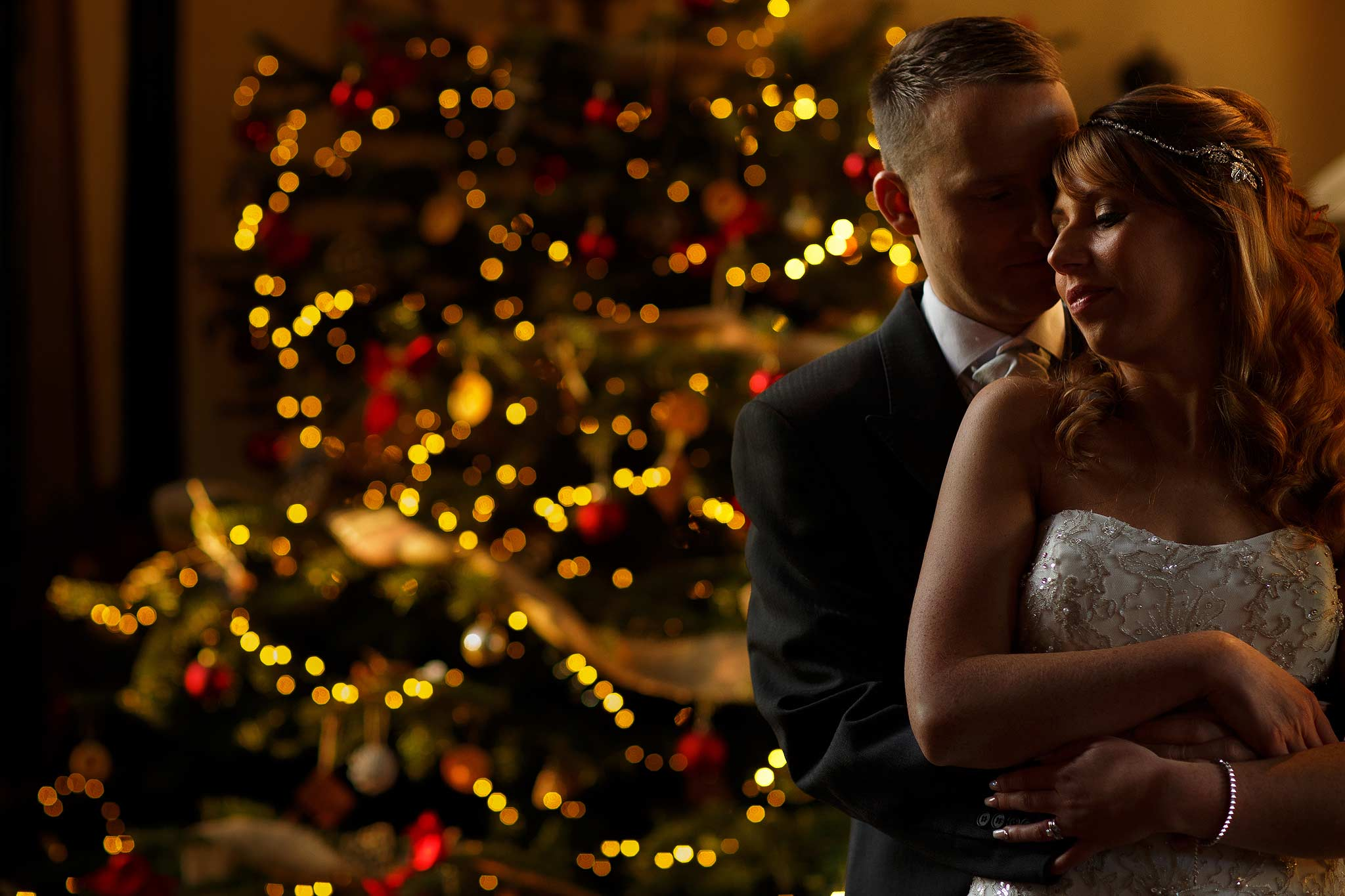 Photograph of a bride and groom in front of the christmas tree at Samlesbury Hall