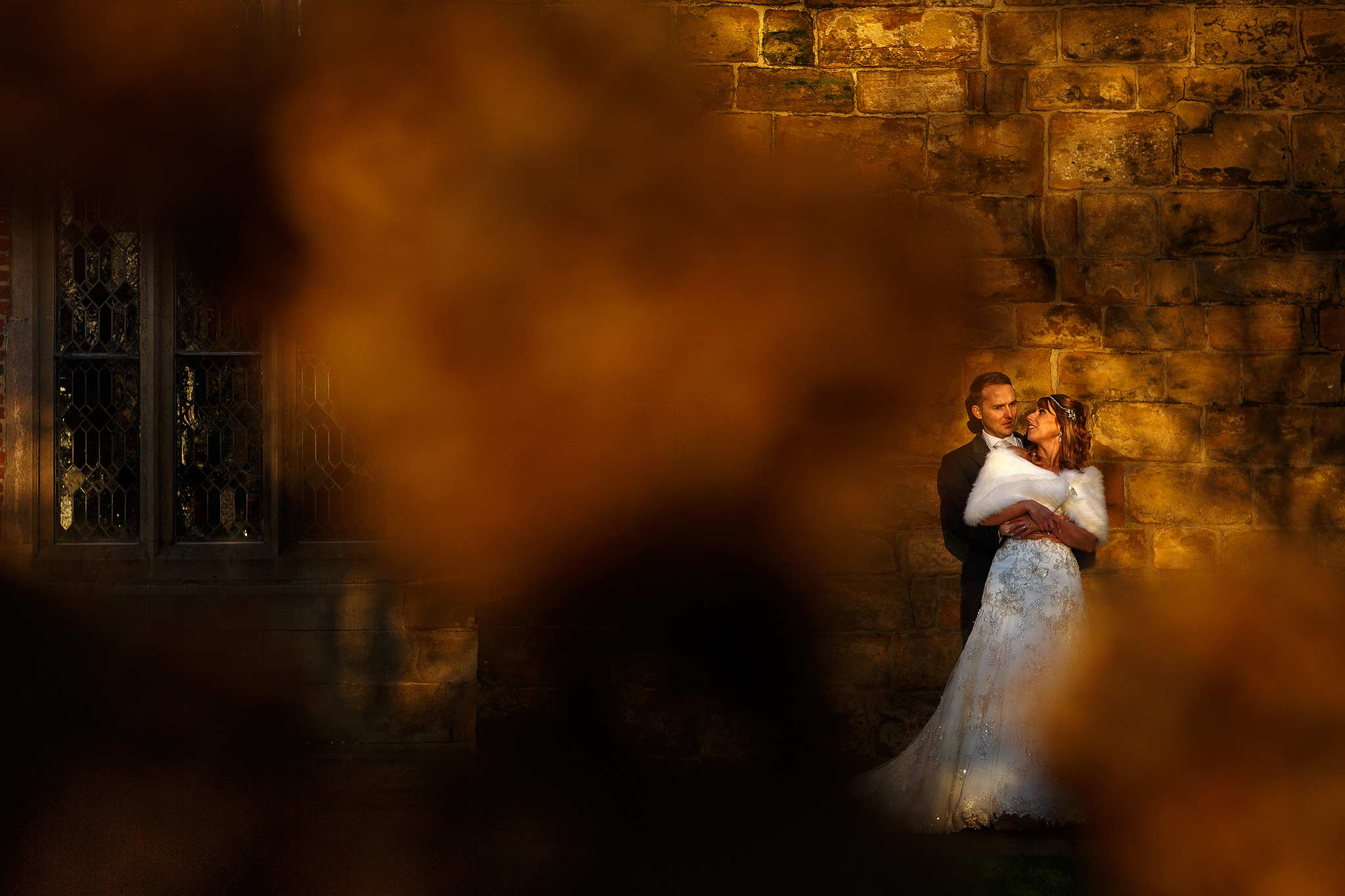 Photograph of a bride and groom laughing in the rose garden at Samlesbury Hall
