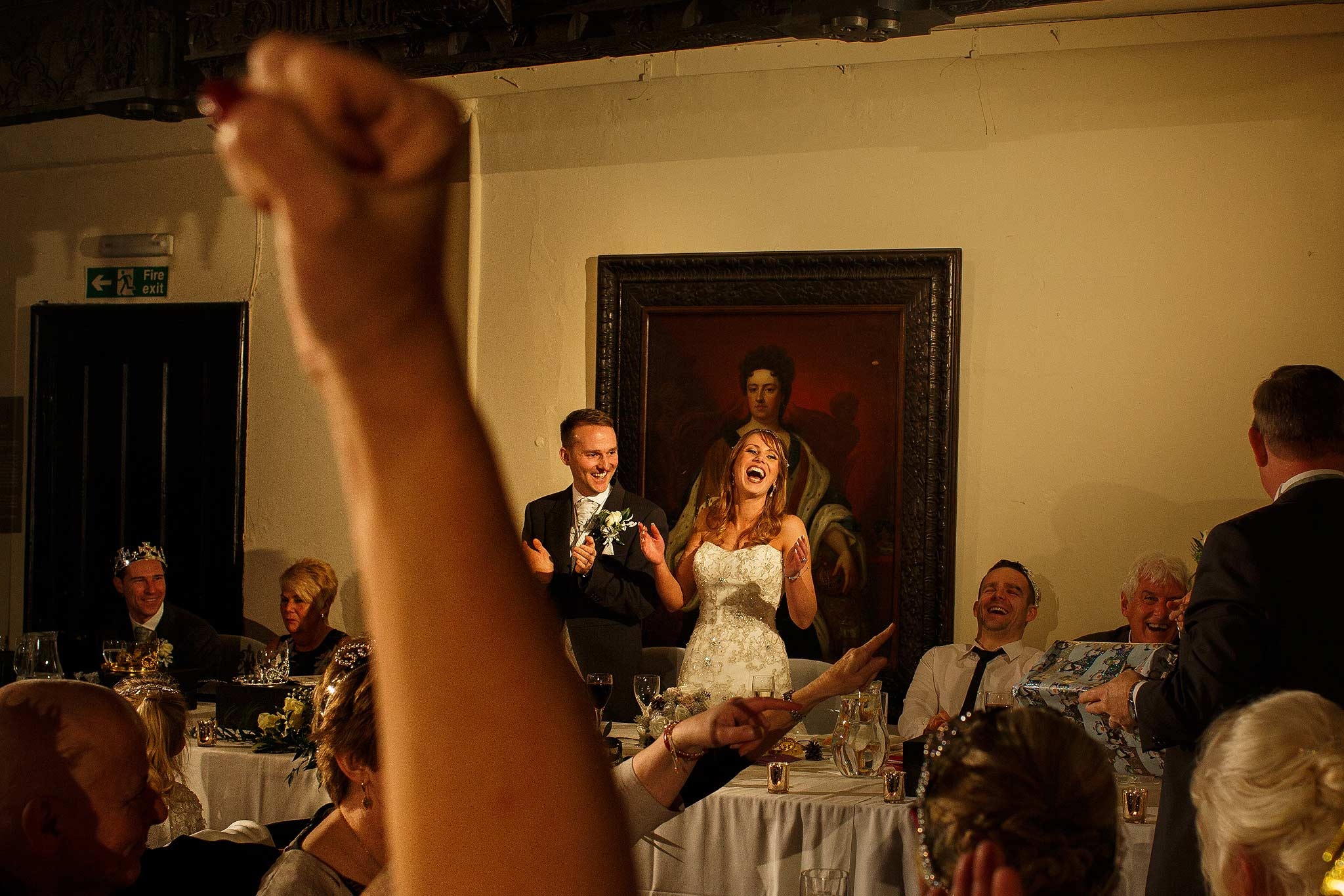 Bride and groom as the guests cheer during speeches at Samlesbury Hall wedding