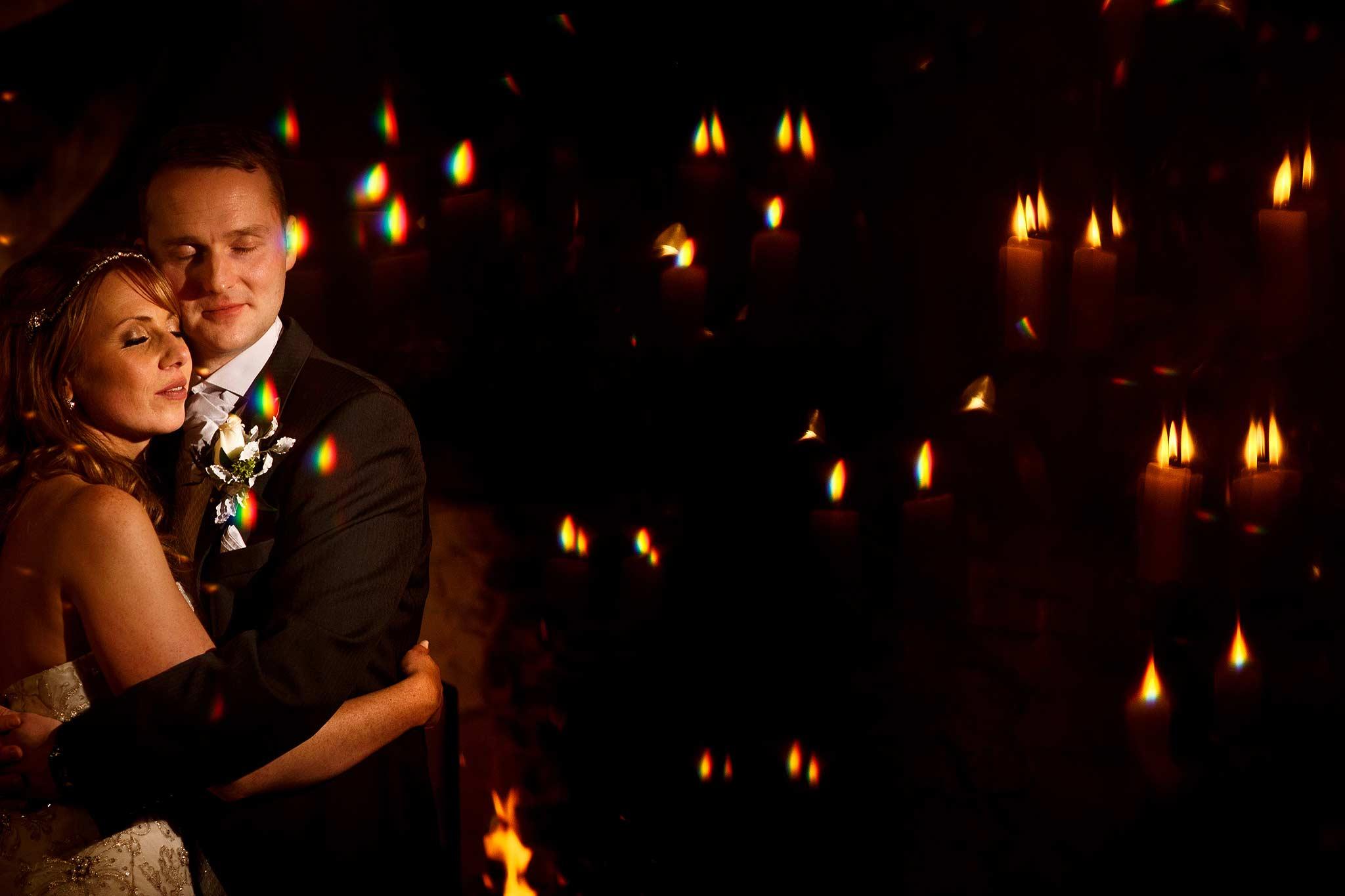 Creative wedding photograph of the bride and groom amongst all the candles at Samlesbury Hall wedding
