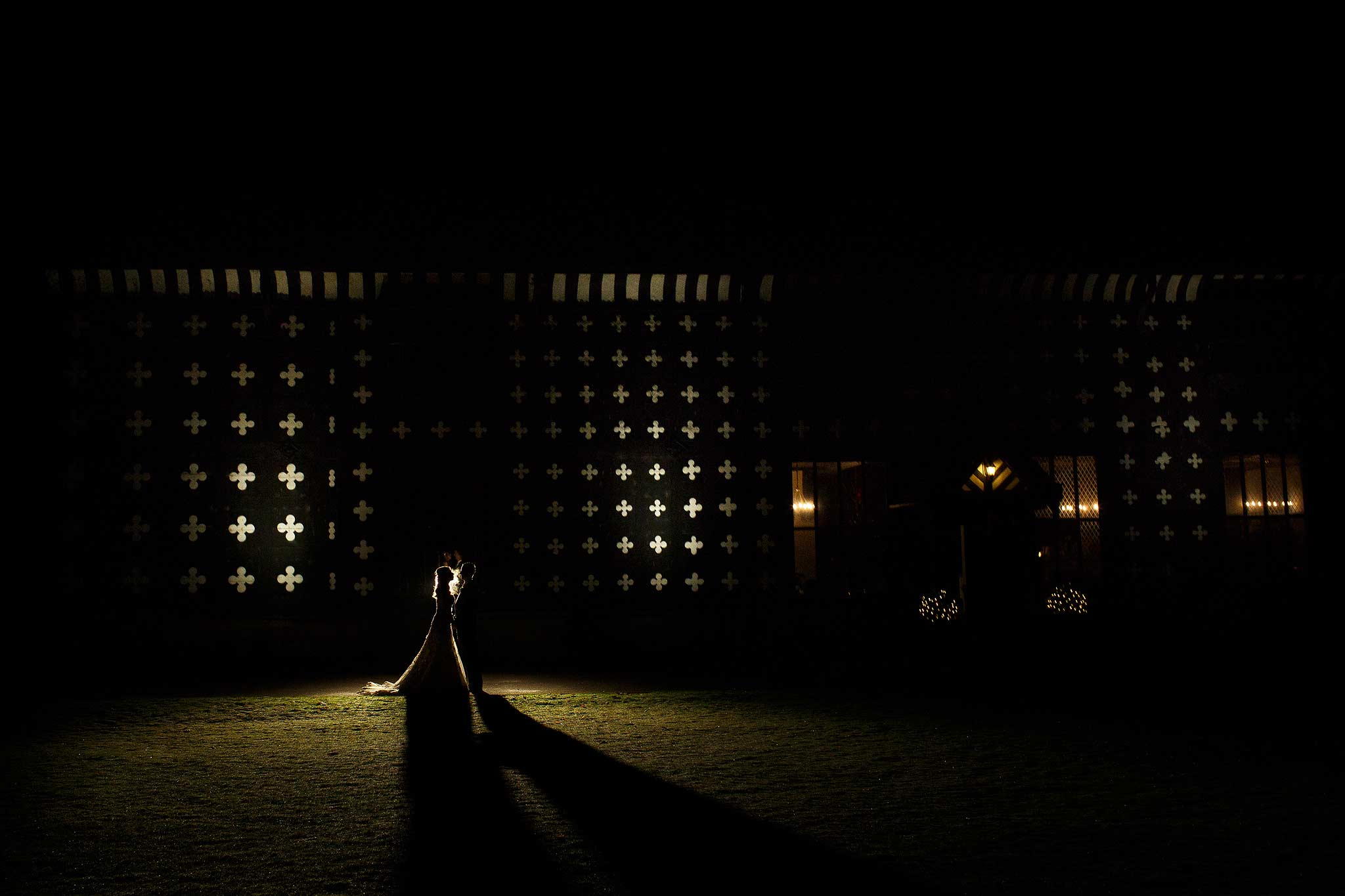 Photograph of the bride and groom outside Samlesbury Hall at night