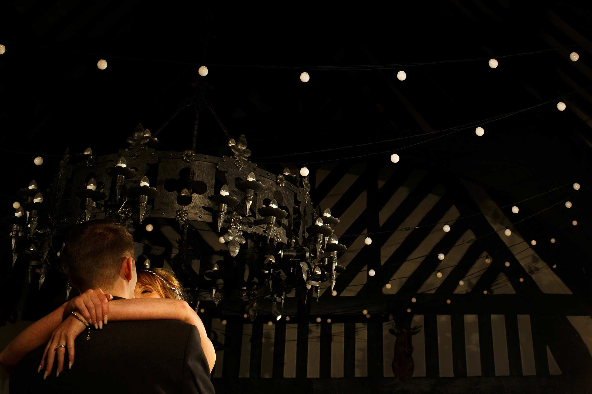 Photograph of the bride and groom during their first dance at Samlesbury Hall showing off the lights on the ceiling