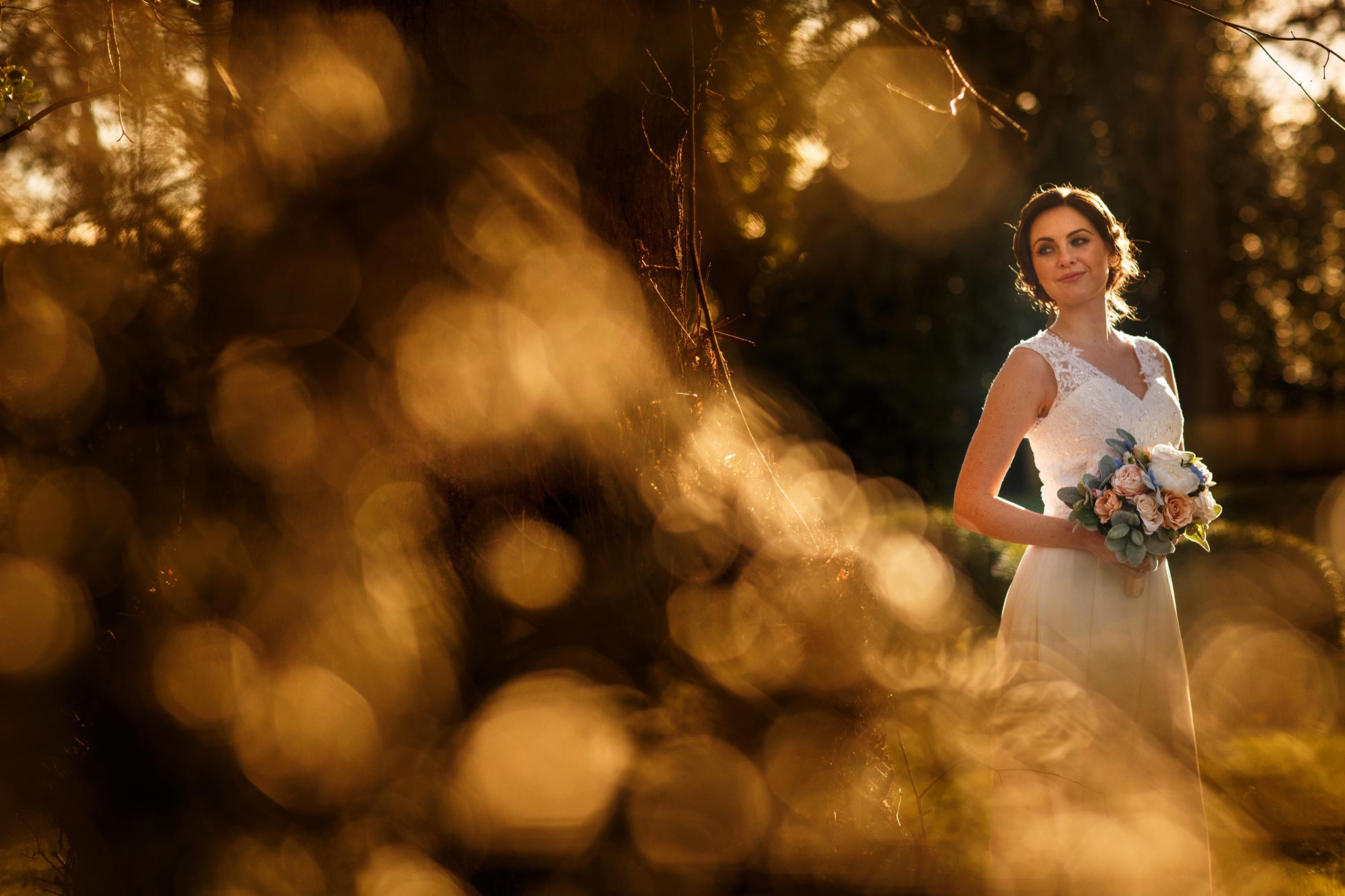Creative wedding photograph of a bride with lots of bokeh in the foreground