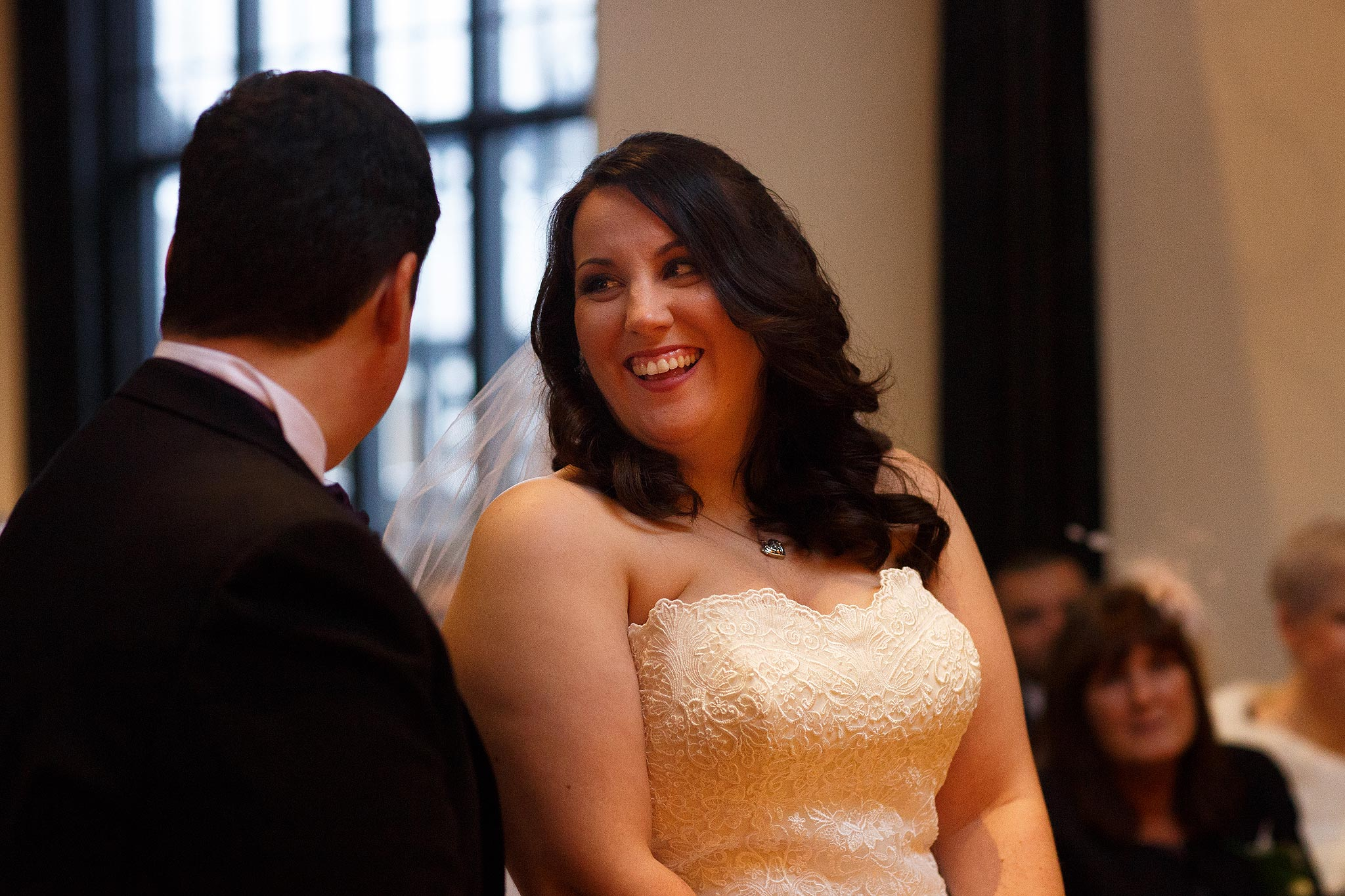 Bride and groom laughing as they say their vows at Samlesbury Hall Wedding