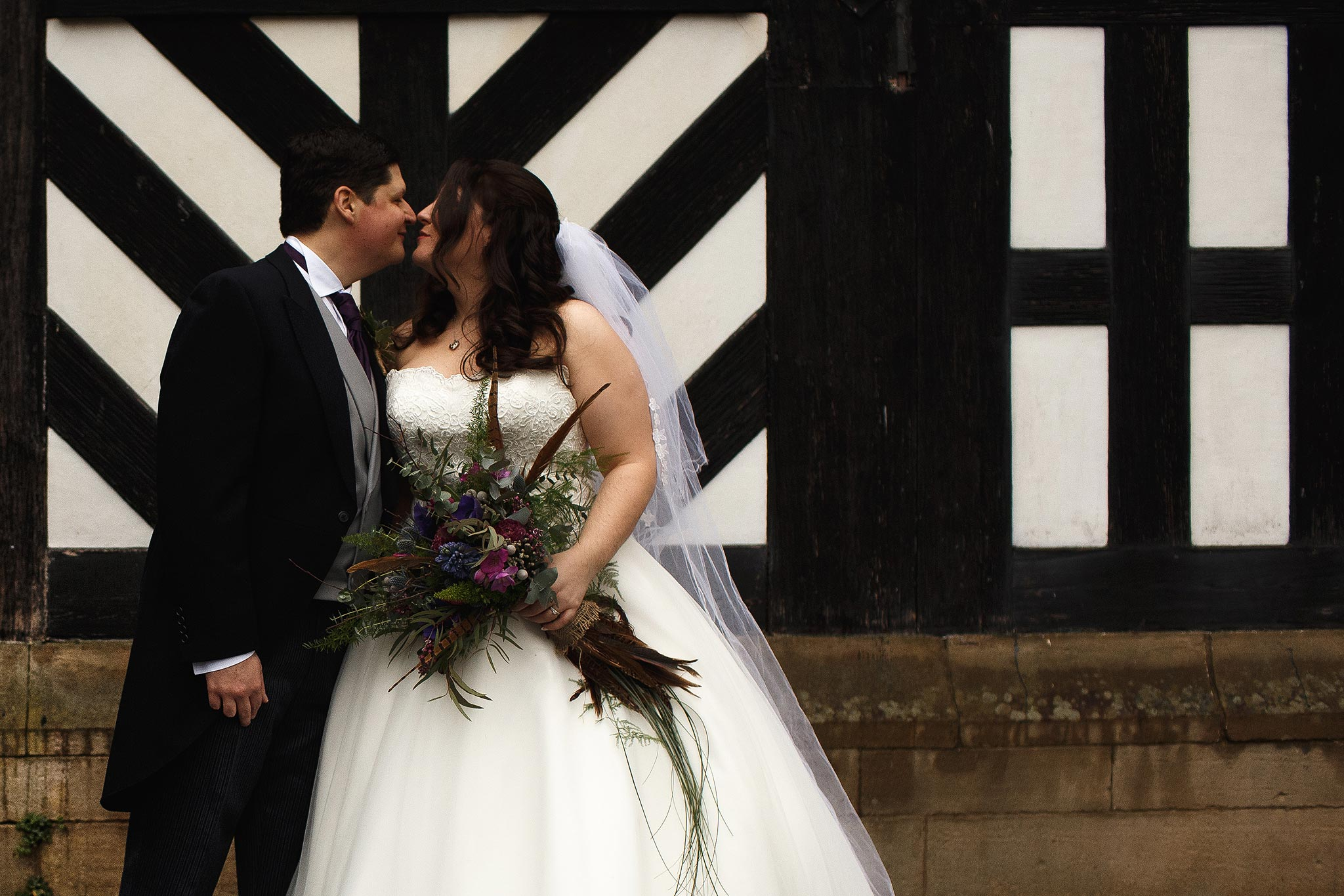 Bride and Groom kissing in front of Samlesbury Hall on their wedding day.