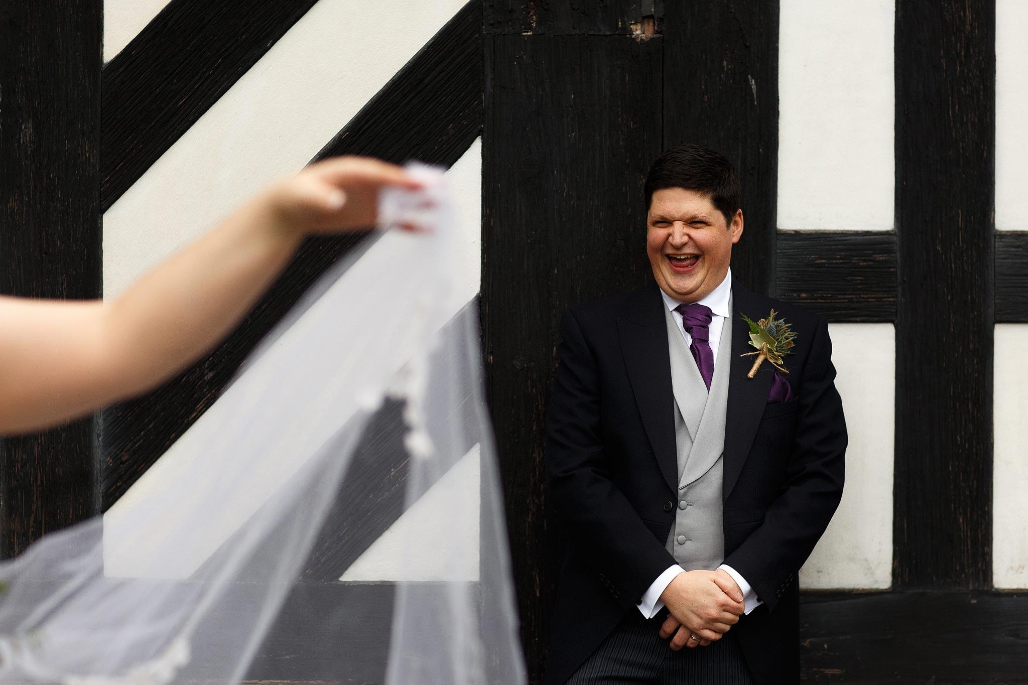 Groom laughing outside Samlesbury Hall on his wedding day.