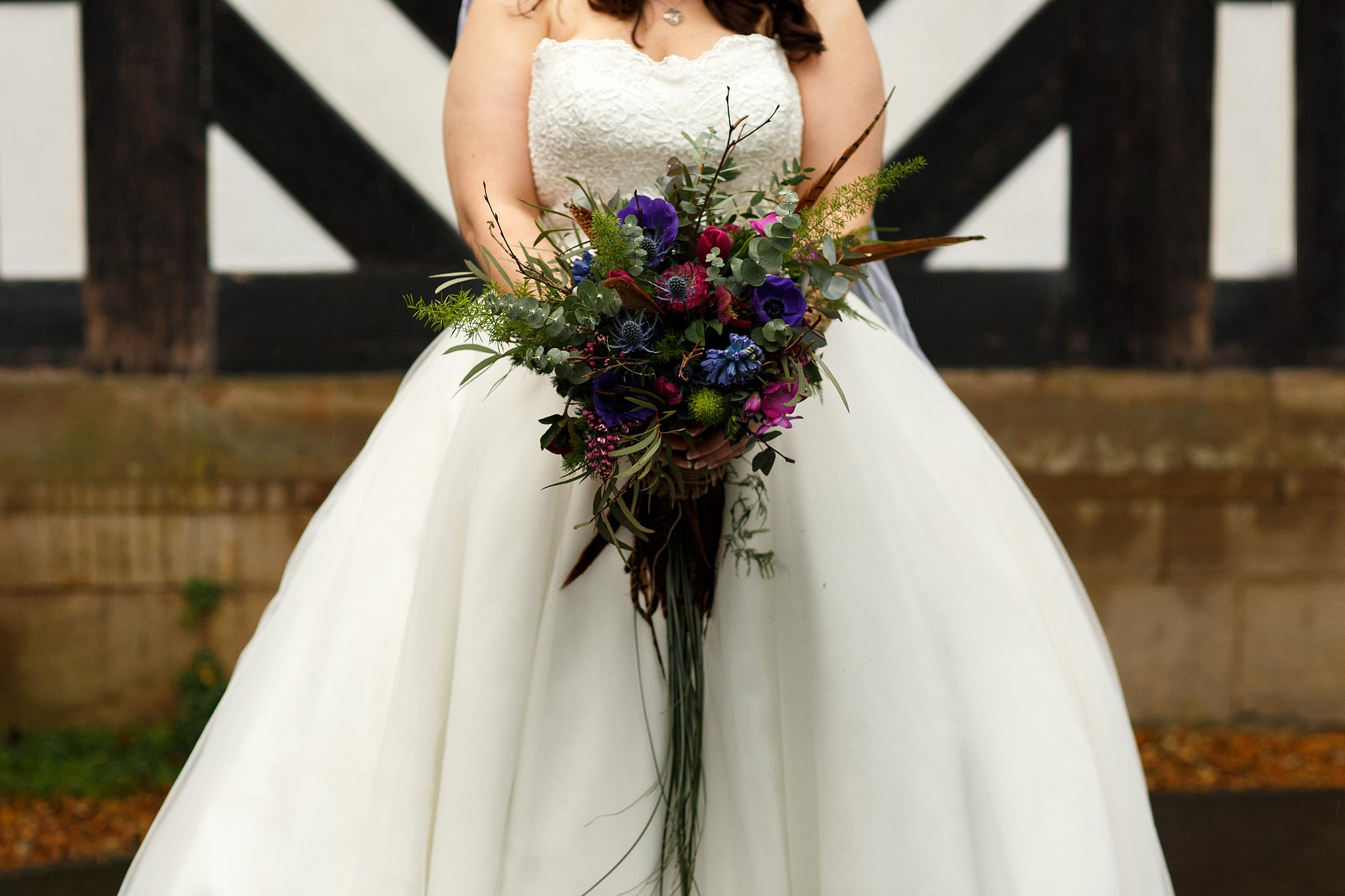 Bride showcasing her feather bouquet at her Samlesbury Hall Wedding