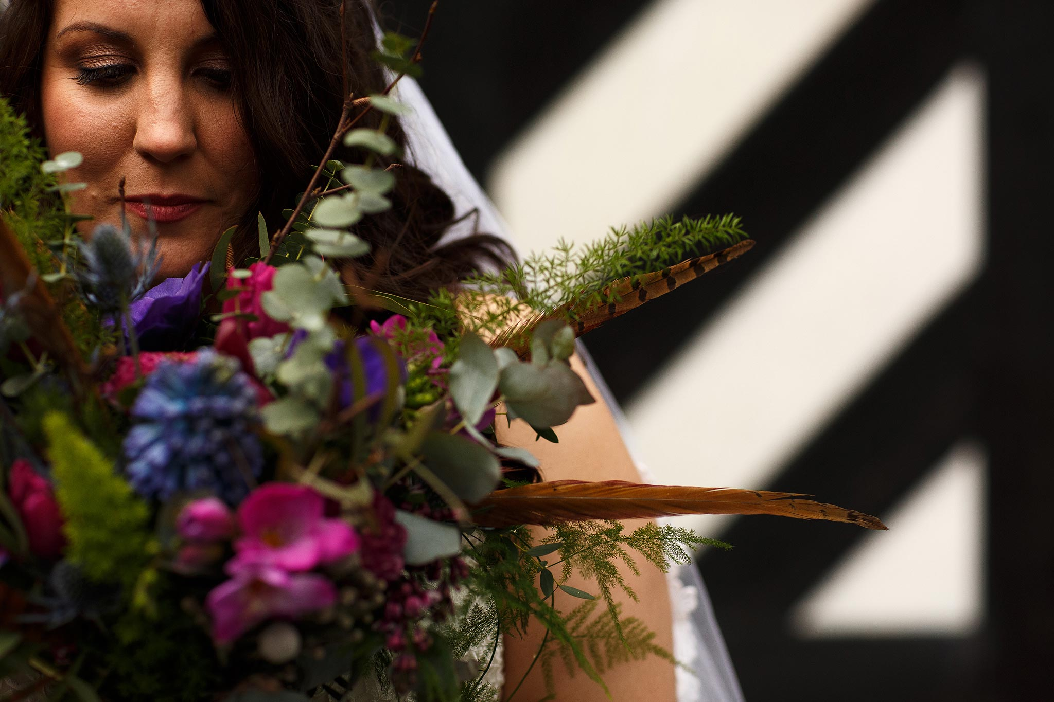 Close up of the bride hiding behind her bouquet at Samlesbury Hall Wedding