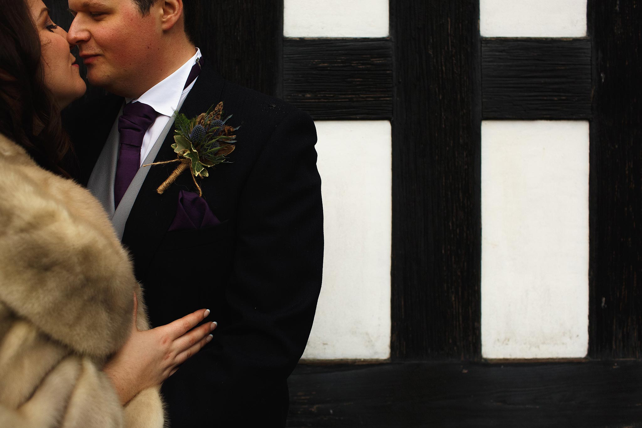 Bride and Groom kissing outside the black and white exterior of Samlesbury Hall