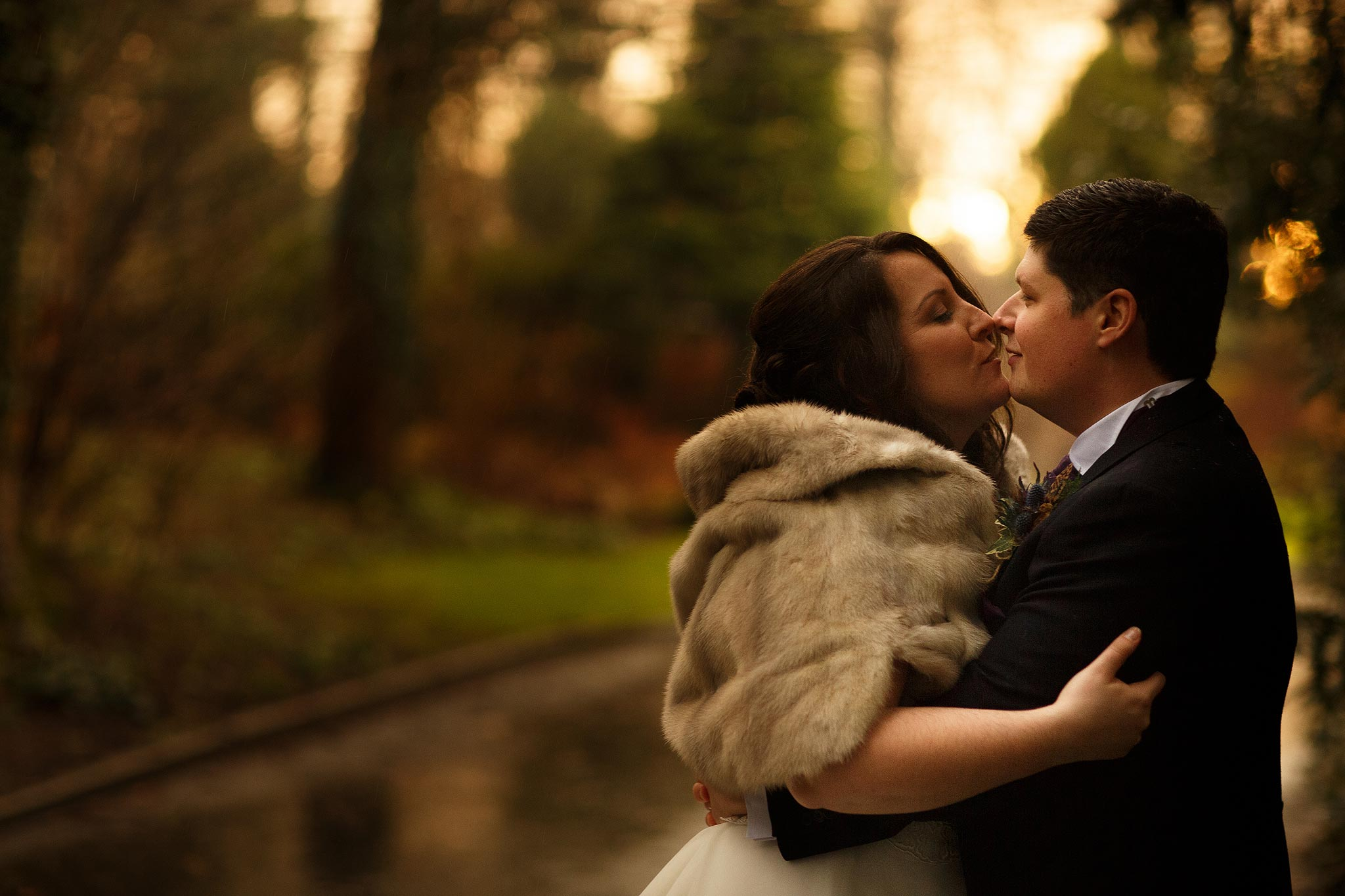 Bride and groom kissing in the rain outside Samlesbury Hall in winter