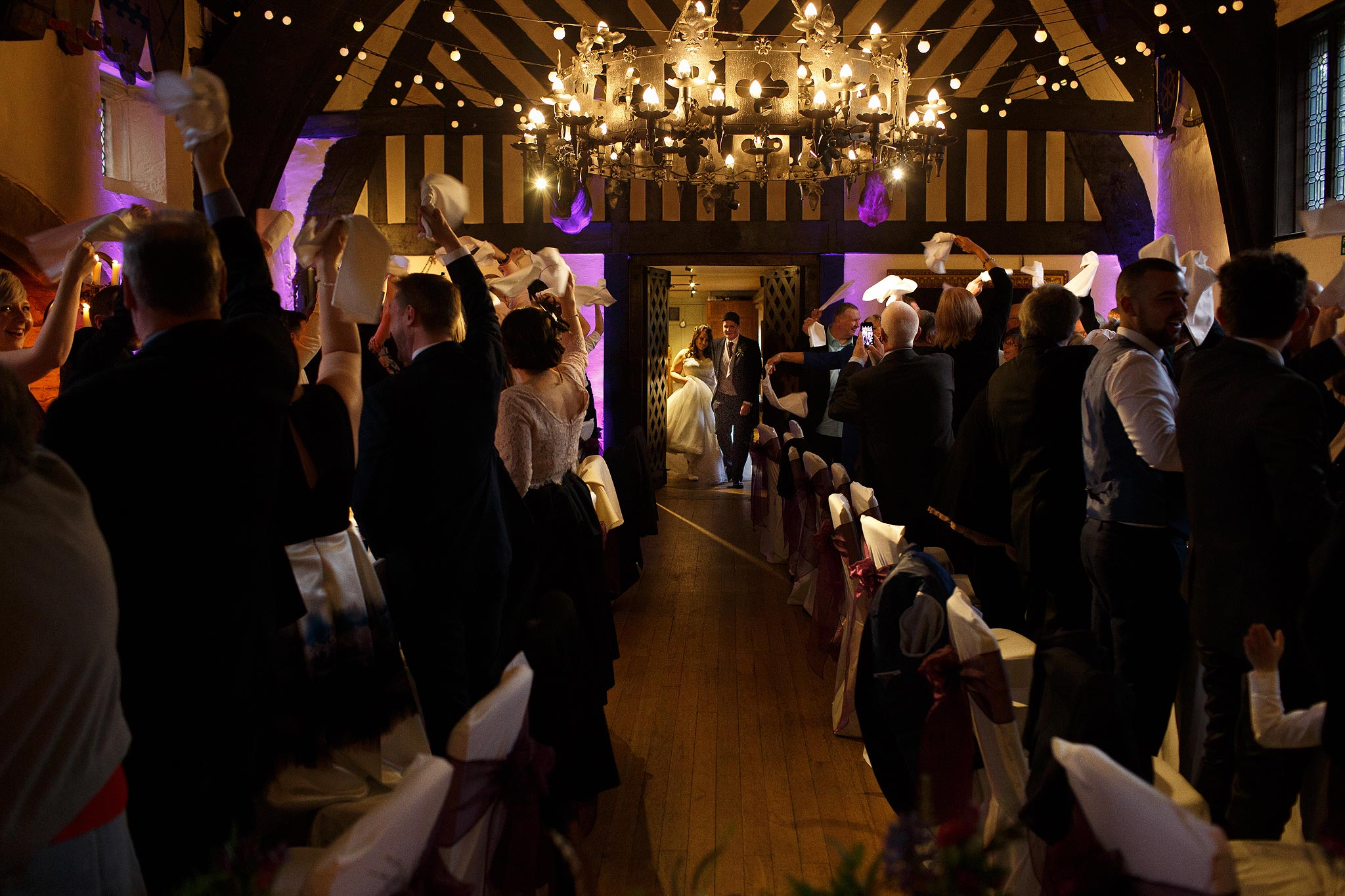Wedding guests swinging napkins as the bride and groom enter the wedding breakfast at Samlesbury Hall