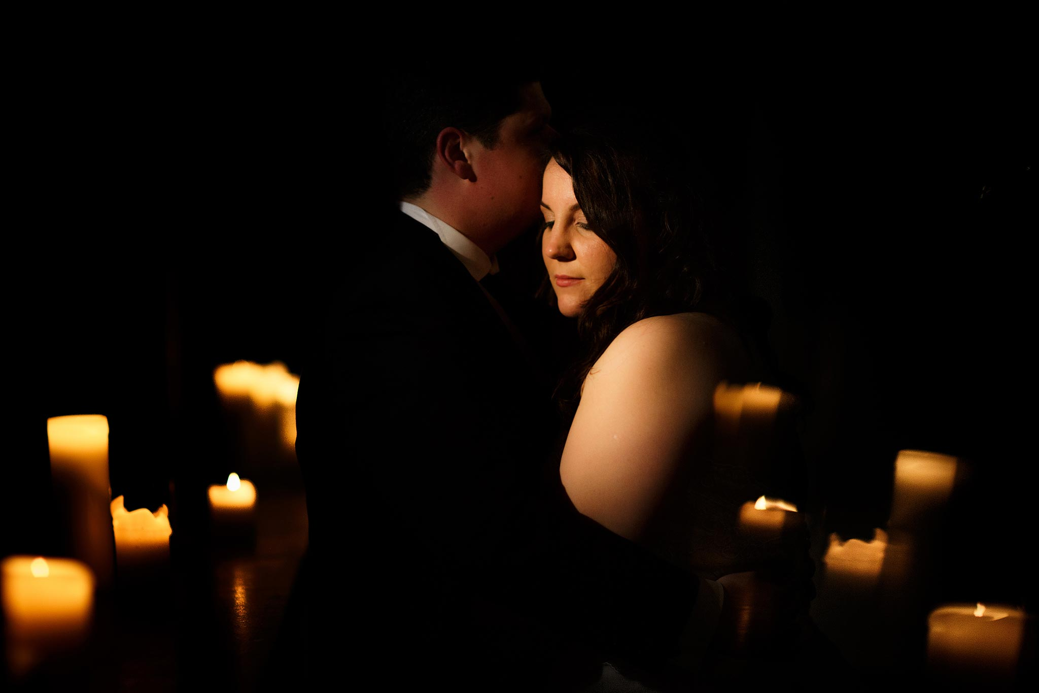 Creative evening portrait of a bride and groom lit by candles at Samlesbury Hall