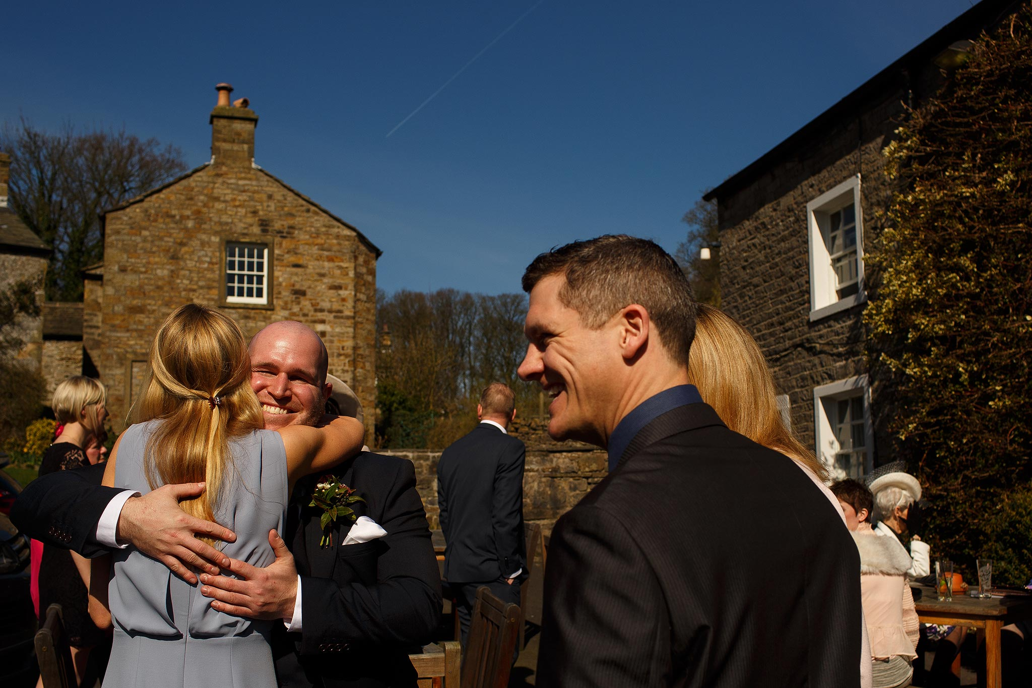 Wedding guests hugging outside the Assheton Arms Downham