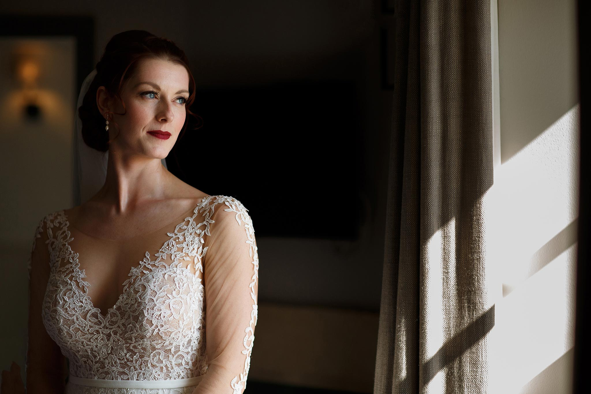 Bride with gorgeous long sleeved dress looking out the window