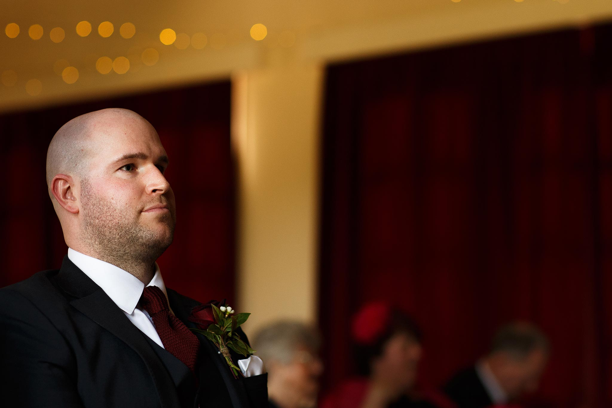 Groom waiting nervously at the top of the aisle at village hall wedding
