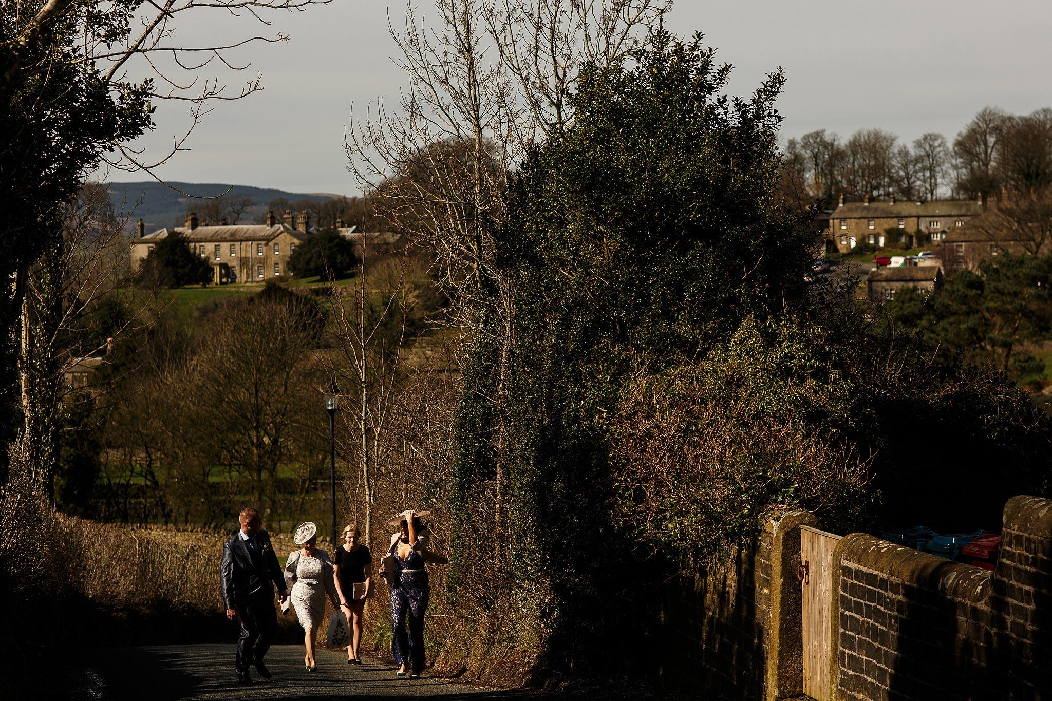 Wedding guests walking through Downham to the village hall