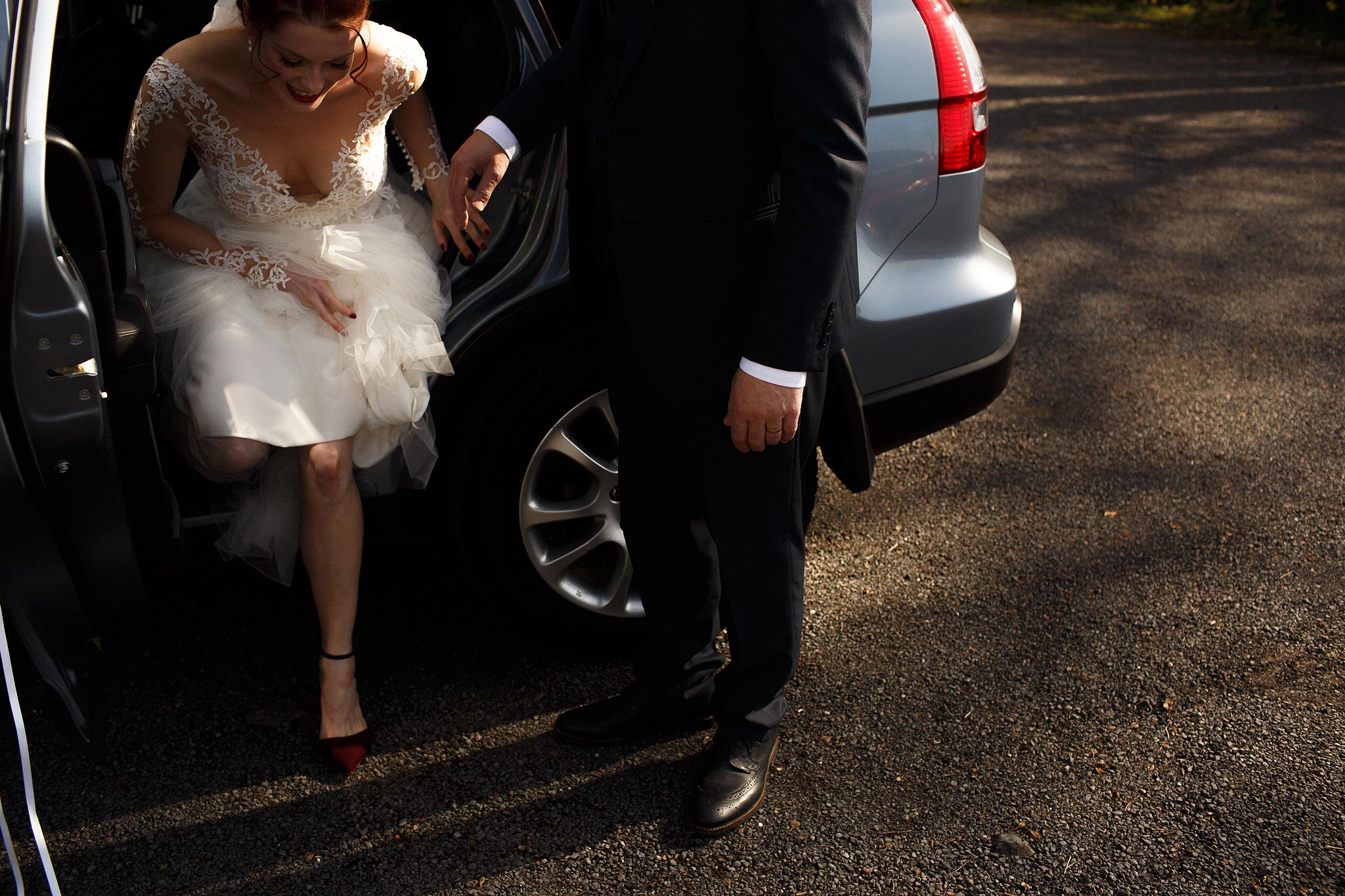 Bride getting out the car at Downham Village Hall