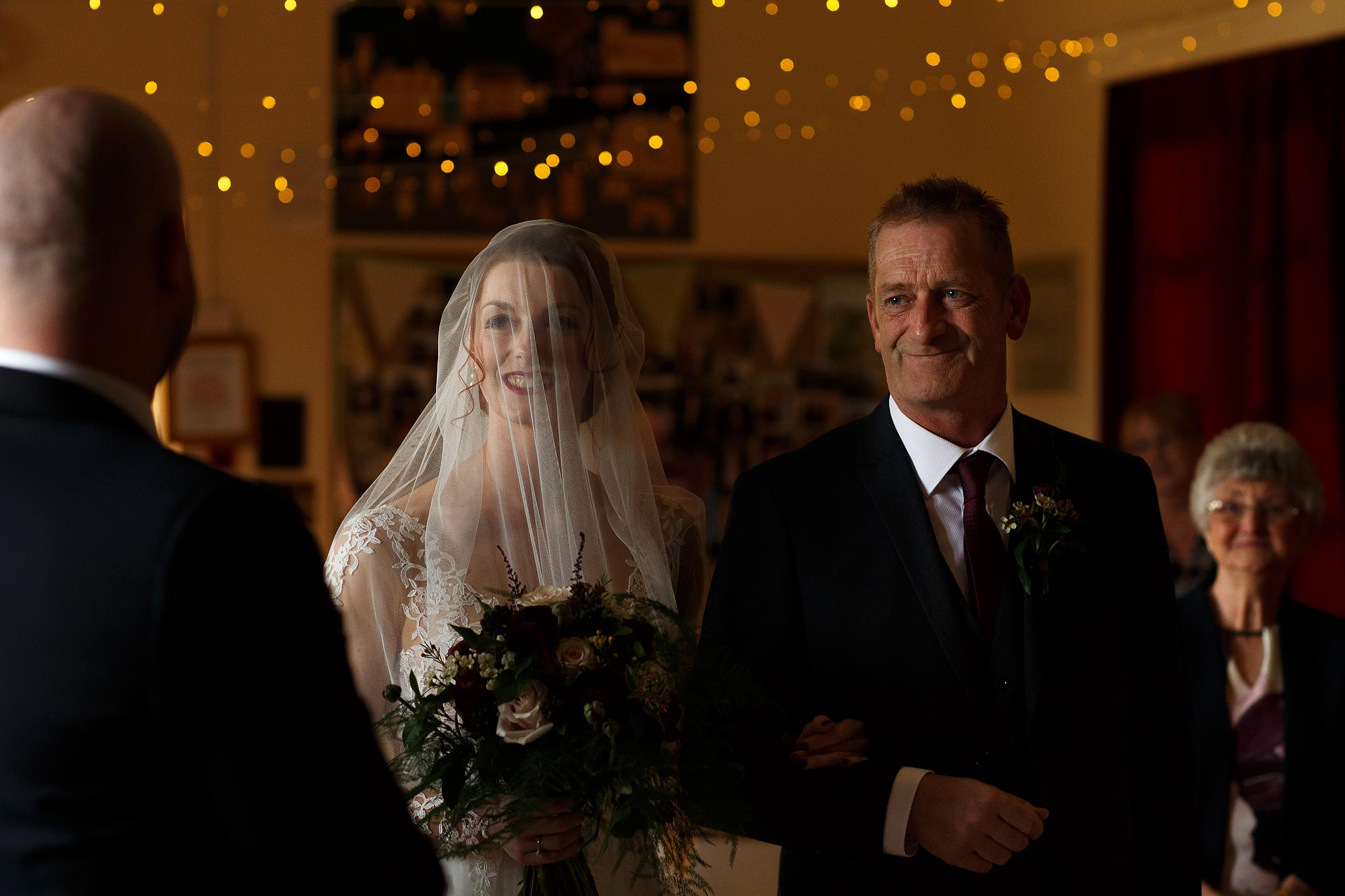Bride looking emotional walking down the aisle with her veil over the face