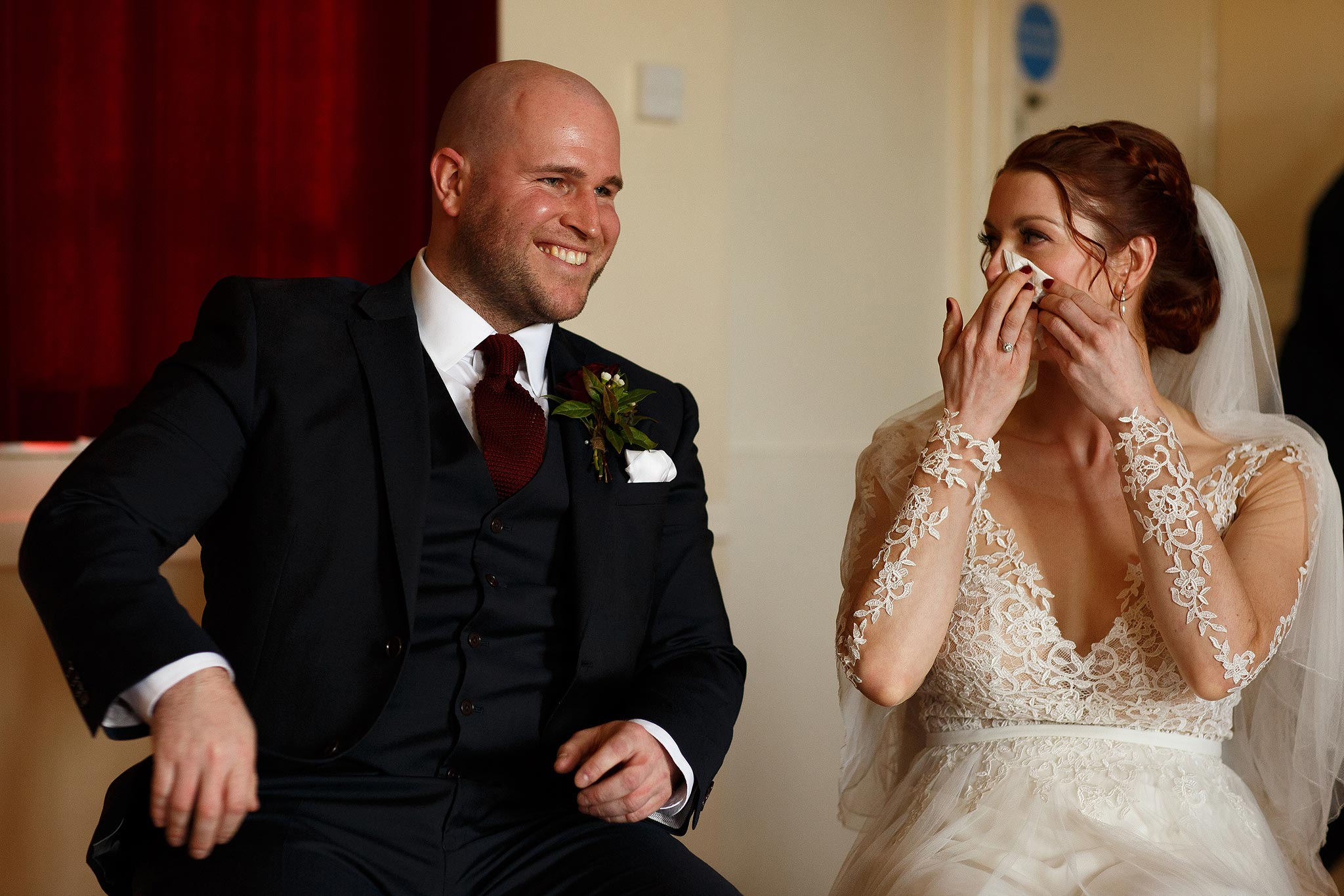 Emotional bride and groom during wedding ceremony at Downham Village Hall