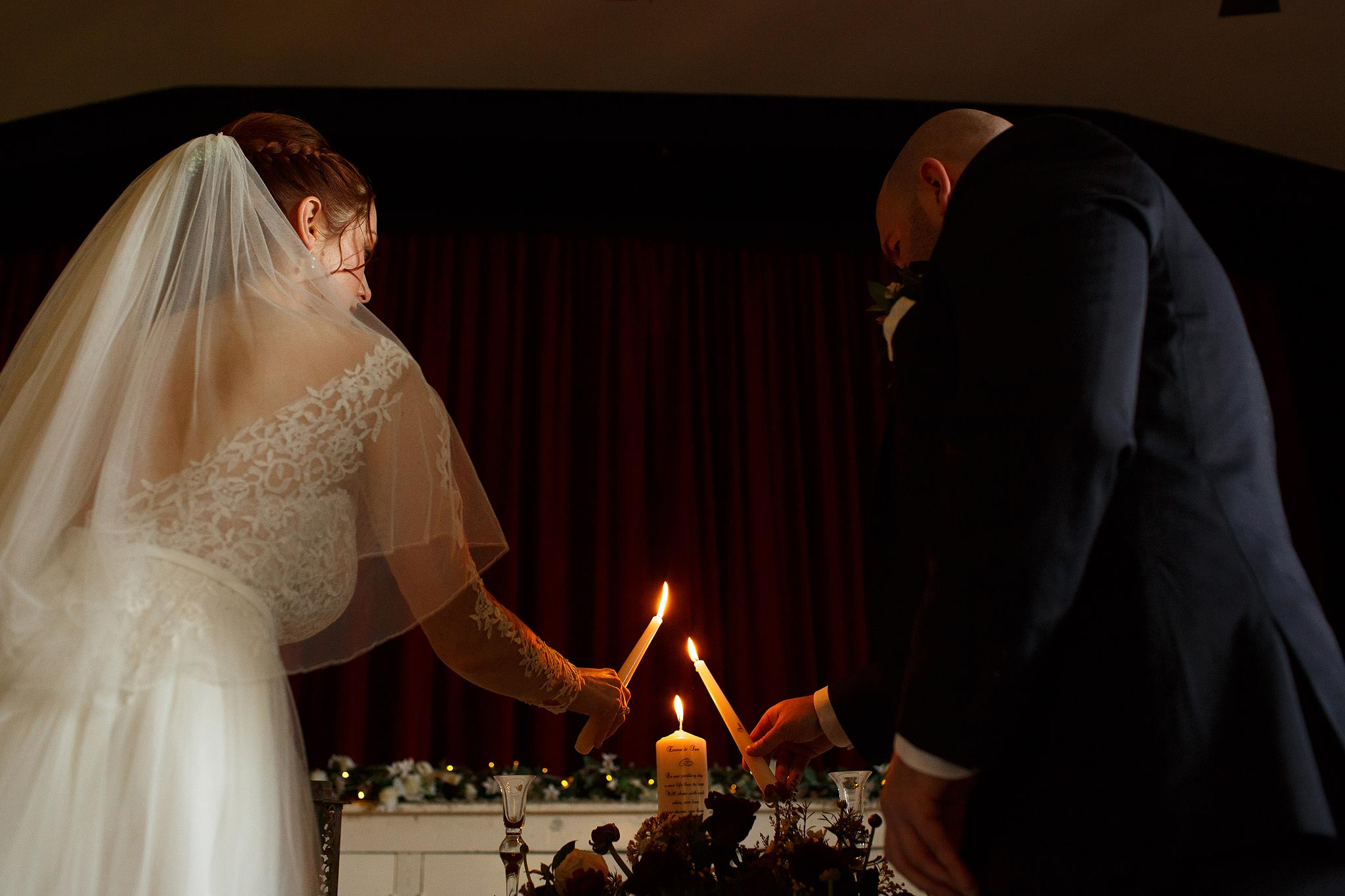 Bride and groom lighting candles during their humanist ceremony at Downhall Village Hall