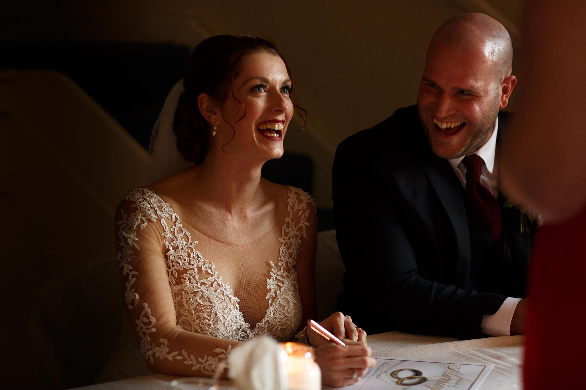 Bride and Groom laughing as they sign the register at Downham Village Hall