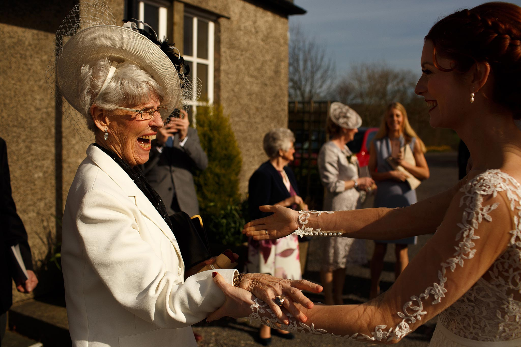 Guests congratulating the bride and groom after their wedding ceremony at Downham Village Hall