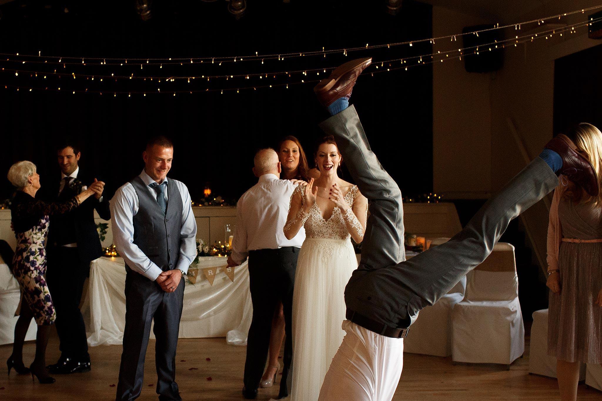 Wedding guests doing handstands on the dance floor at Downham Village Hall wedding