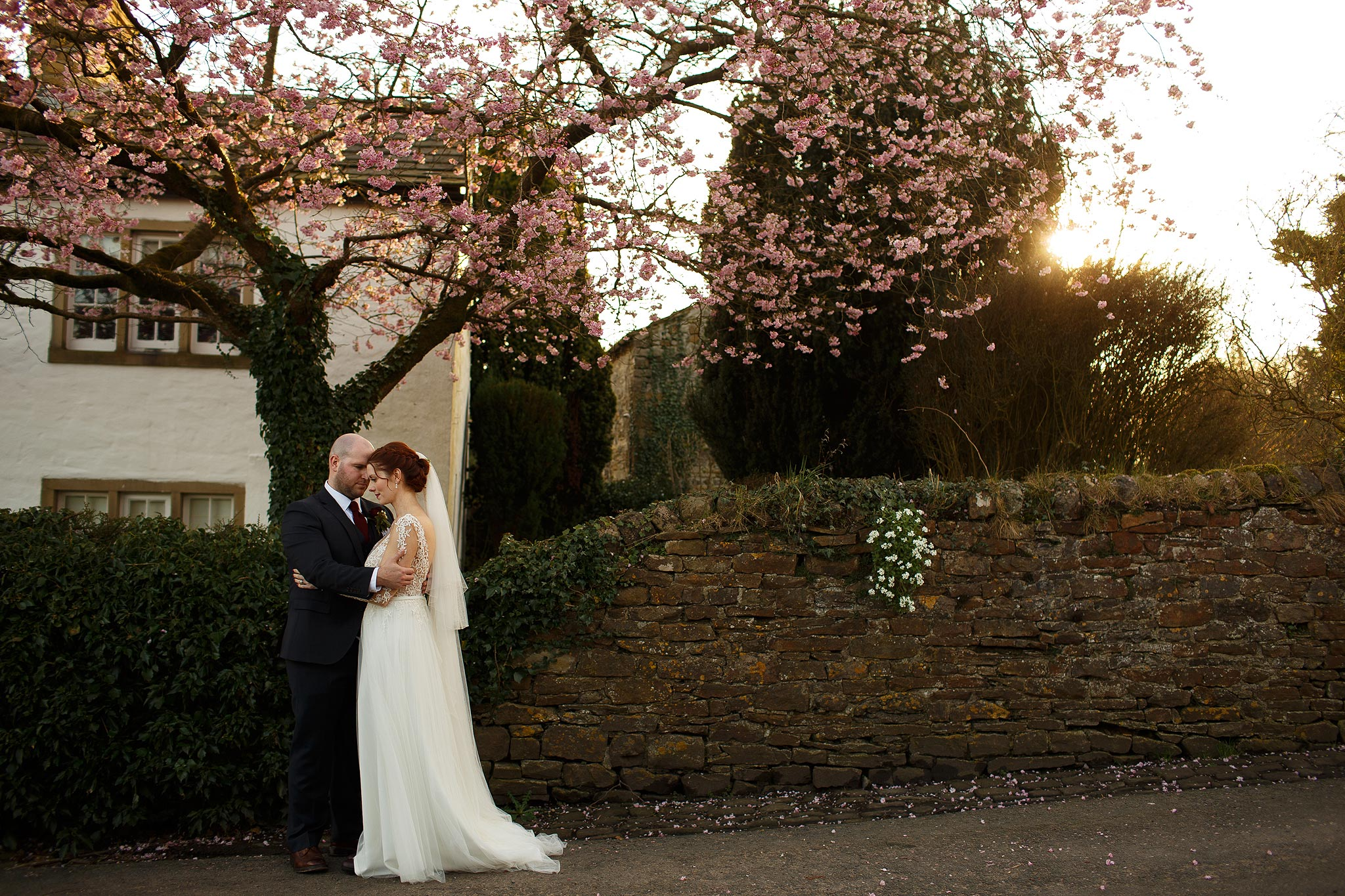 Bride and groom stood under the blossom tree in Downham on their wedding day.