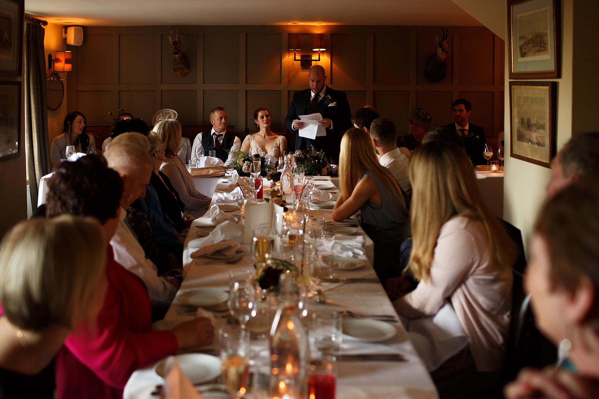 Wide photograph of all the guests during speeches at Assheton Arms wedding
