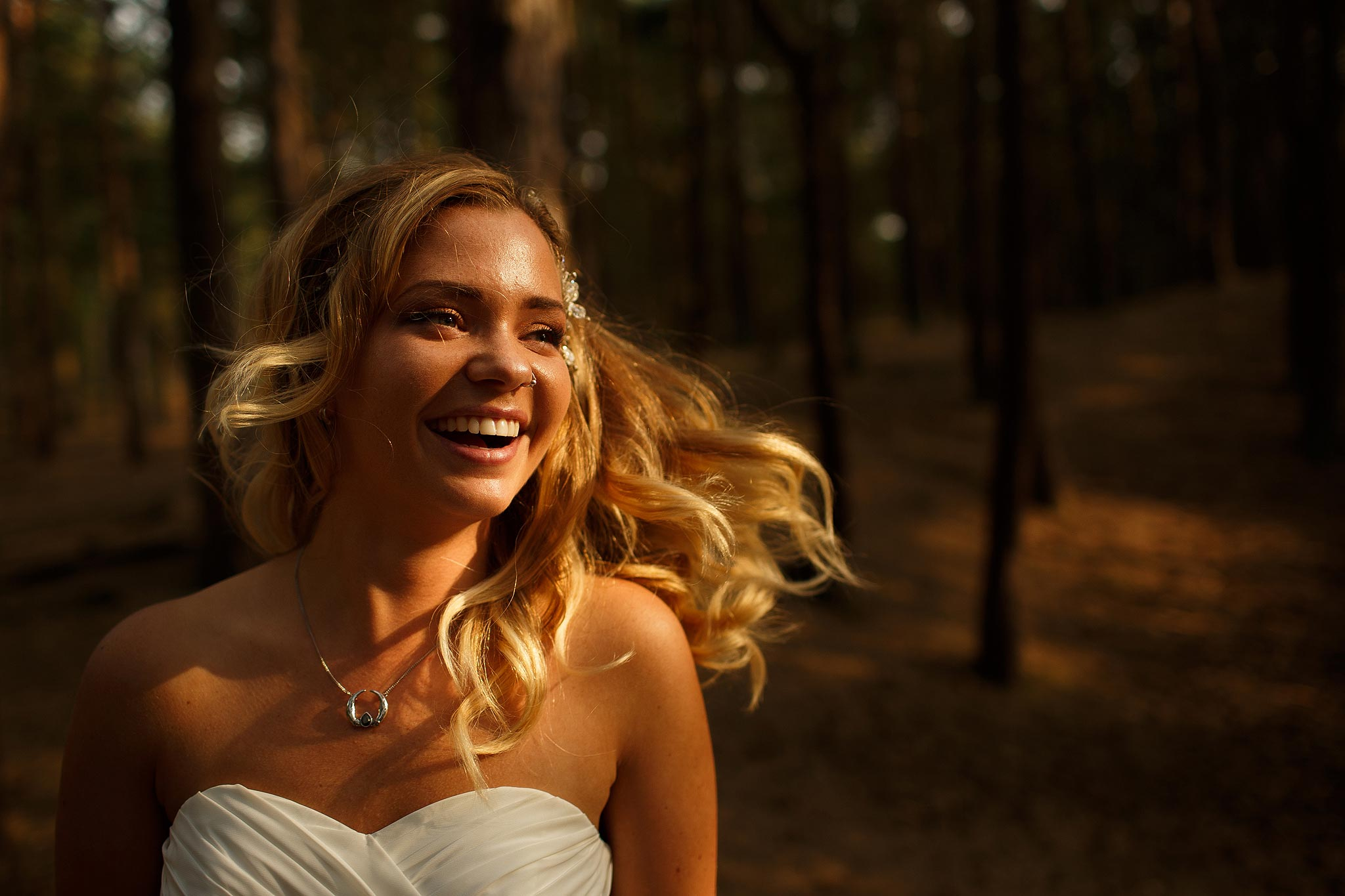 Bride laughing with flowing hair in the woods
