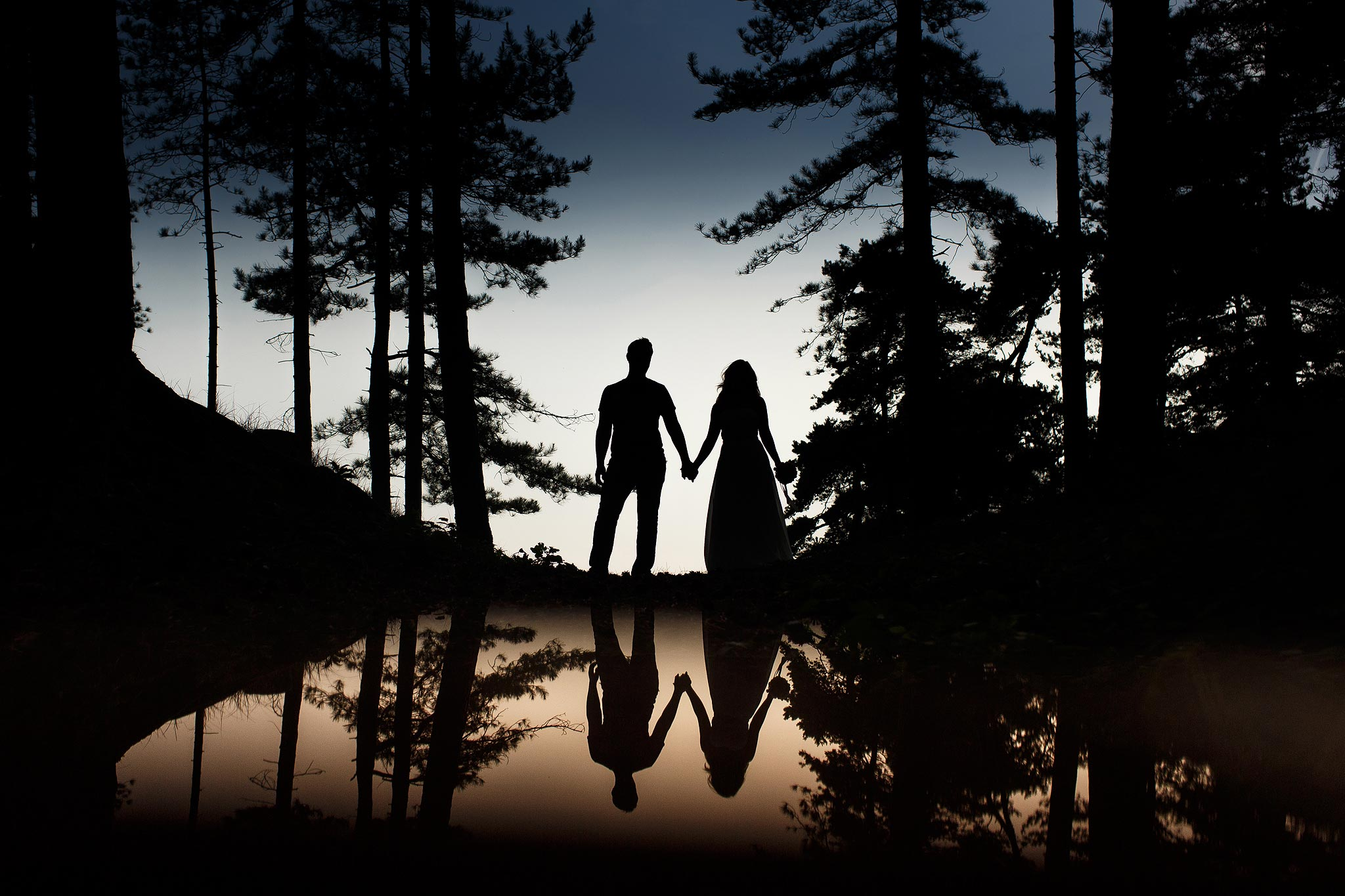 Creative reflected silhouette of a bride and groom in woodland