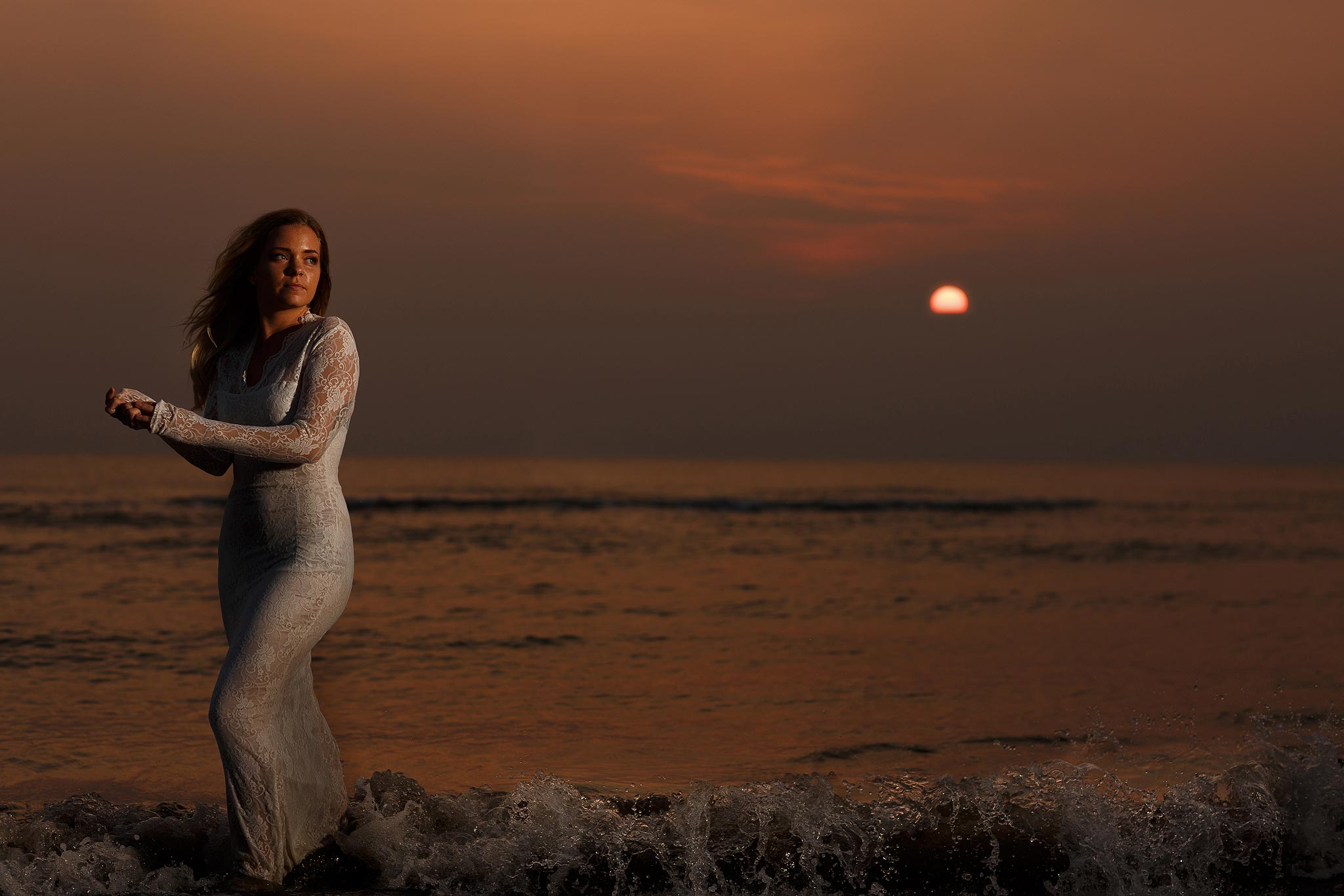 Flash lit photograph of a bride in the sea with the waves coming around her