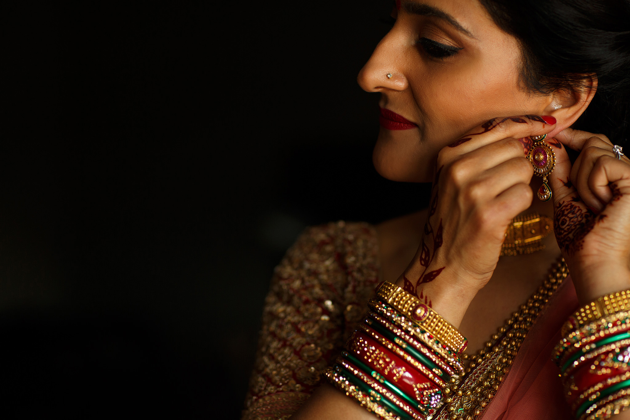 Close up of Indian bride putting her earrings in